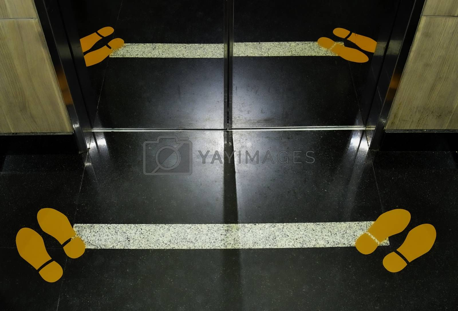 Footprint signage showing social distancing measures on the floor of an elevator.