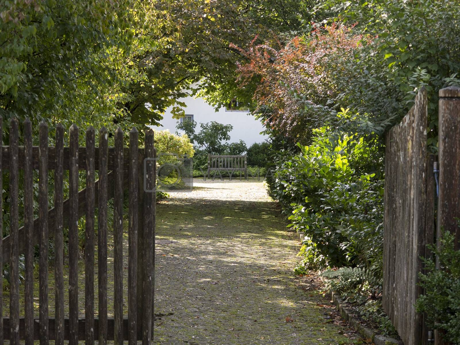 Royalty free image of Open wooden gate and gravel driveway by Kasparart
