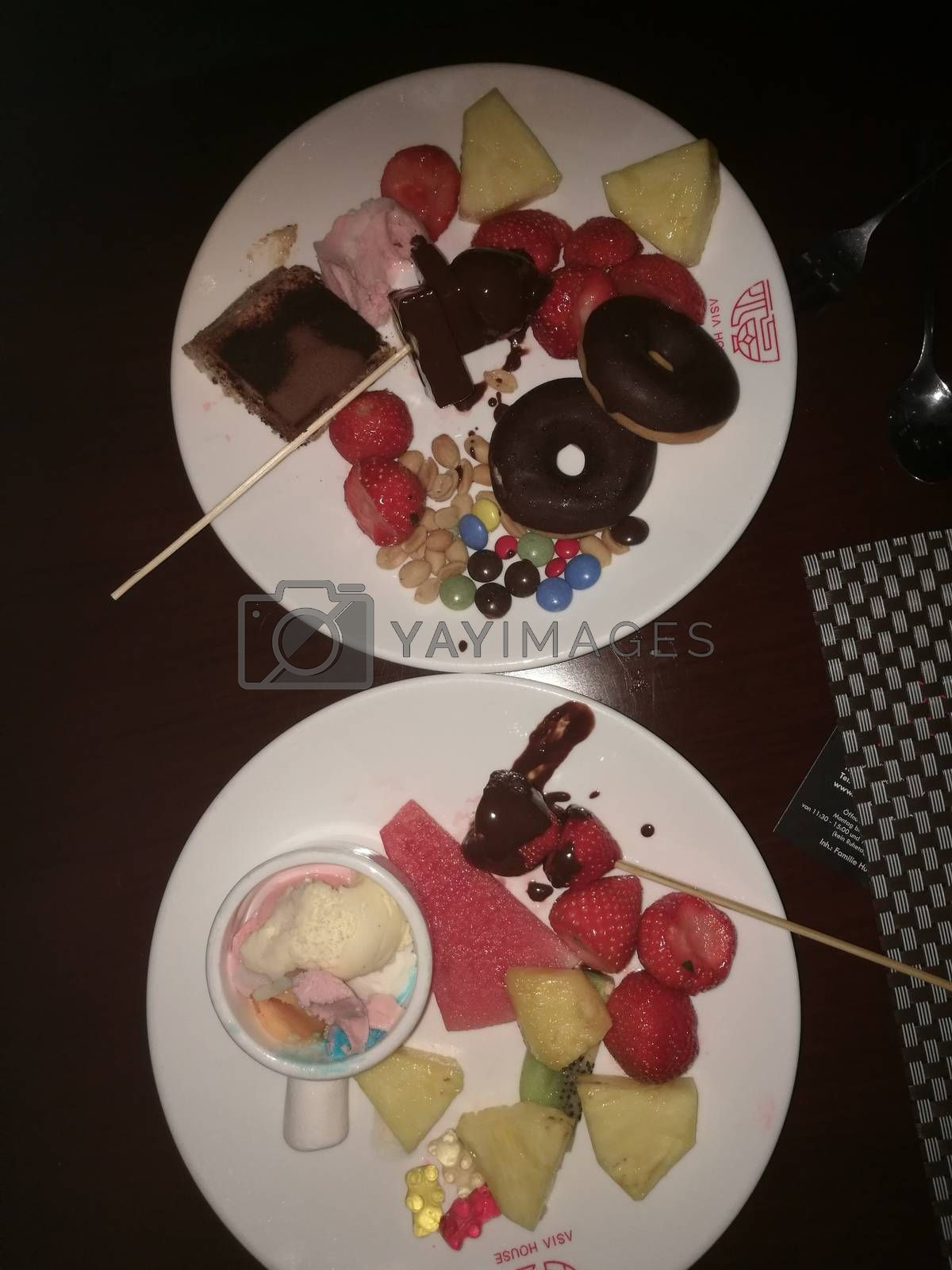Royalty free image of A bowl of donuts and fruit on a plate by balage941