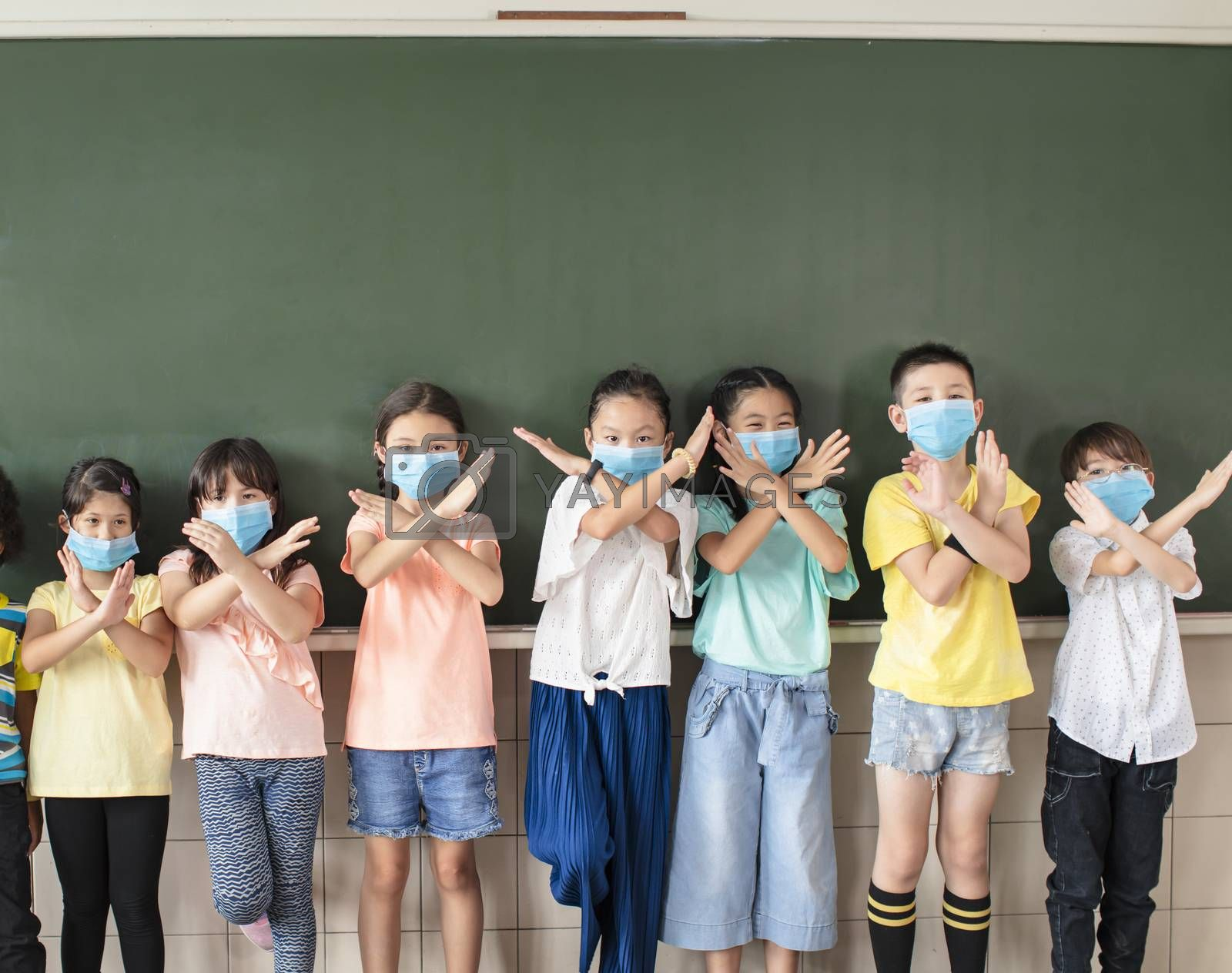 Group of diverse young students wear mask and showing stop sign gesture in classroom