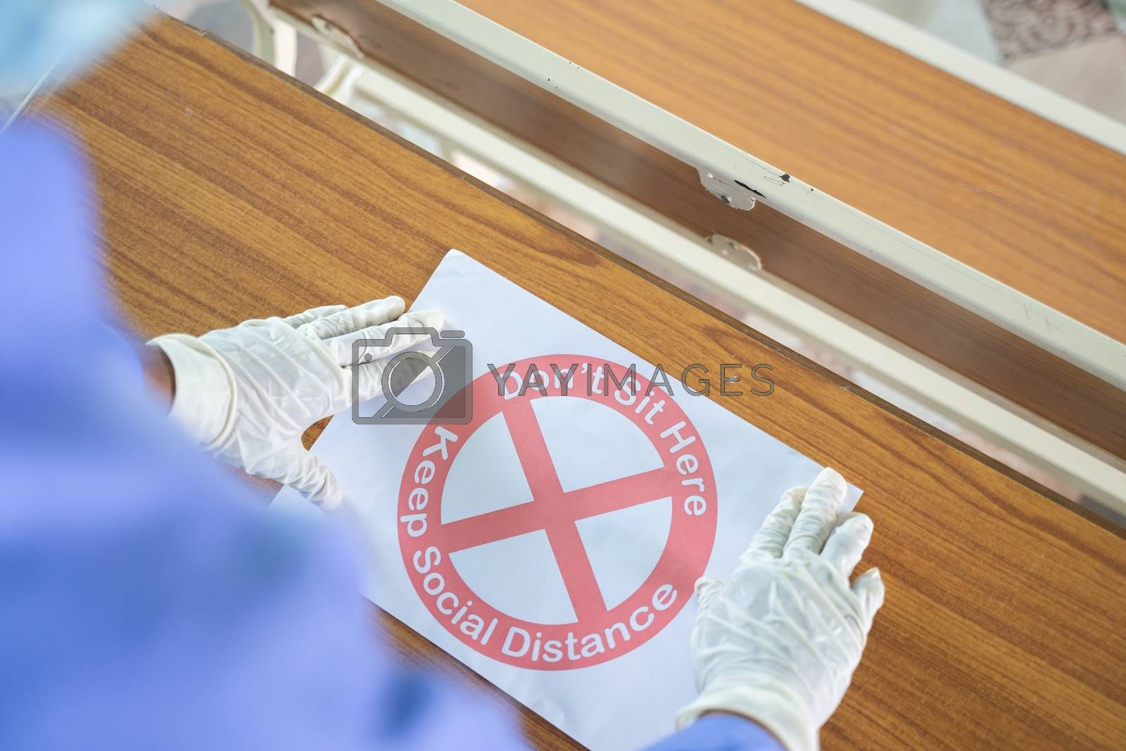 Royalty free image of Shoulder shot of man with medical mask and hand gloves pasting dont sit here keep social distance signage poster on desk surface as coronavirus or covid-19 safety measures at school or college by lakshmiprasad.maski@gmai.com