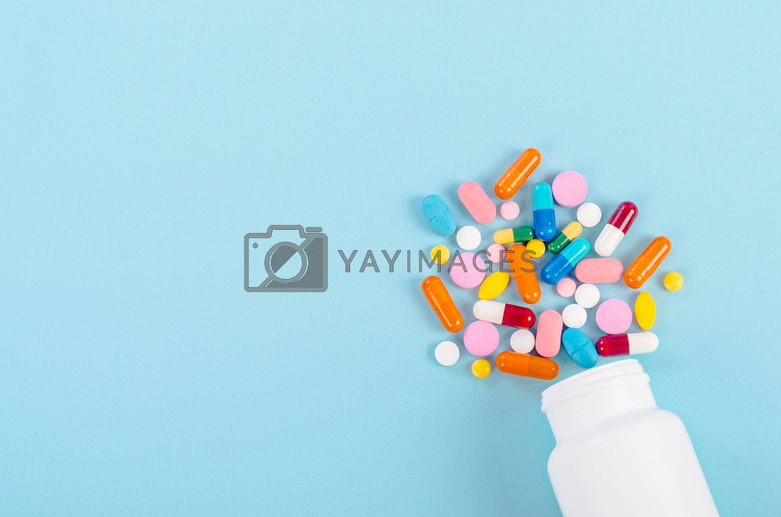Royalty free image of Medical pills and tablets spilling out of a drug bottle. by Gamjai