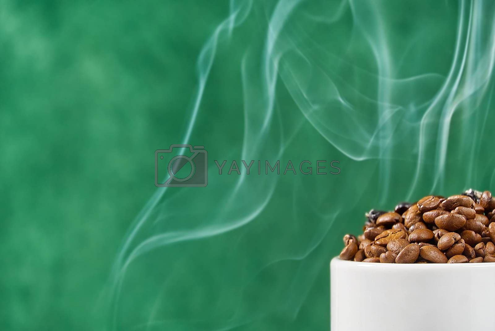 Royalty free image of International day of coffee concept. close-up white coffee cup full of coffee beans on green background with smoke on top. by PhotoTime