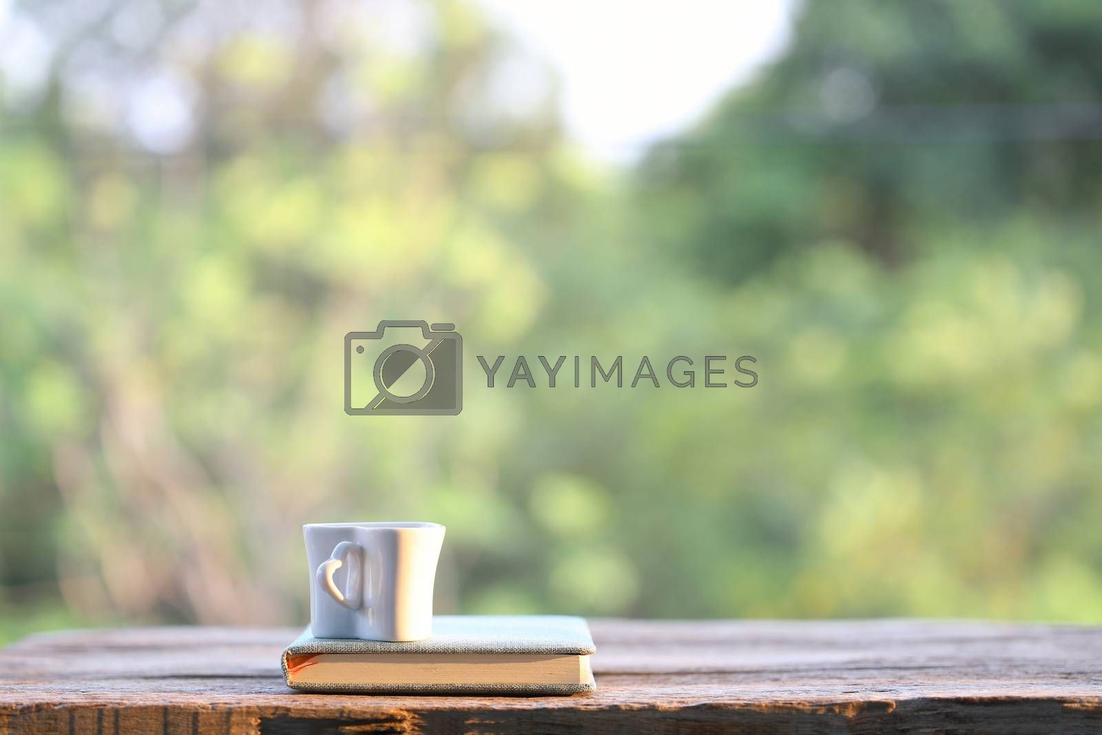 Royalty free image of White cup with notebook on wooden table with nature view by paladin12