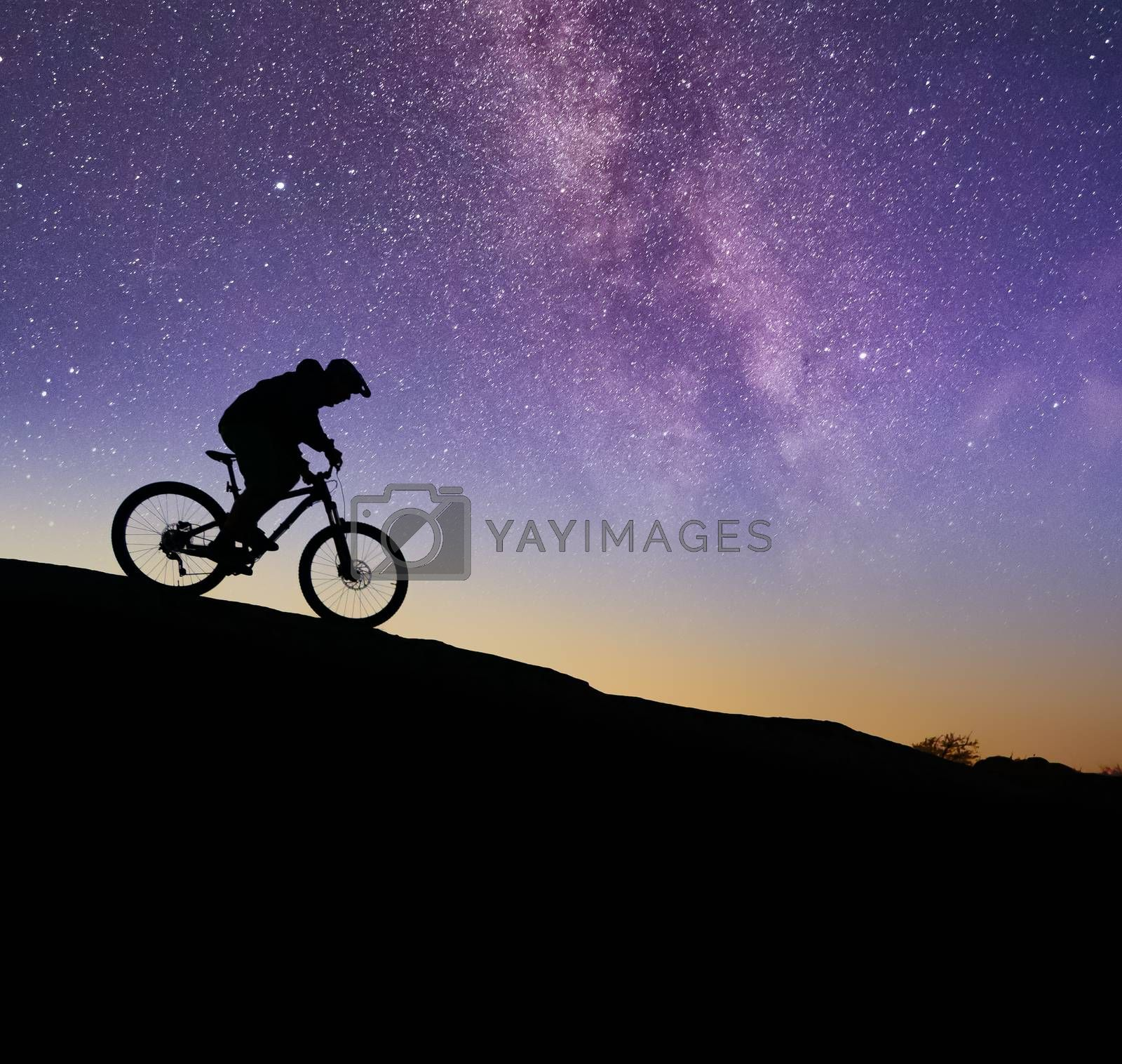 Cyclist Riding the Bike on the Rock Under the Night Sky with Bright Milky Way. Extreme Sport, Active Lifestyle and Adventure Concept.