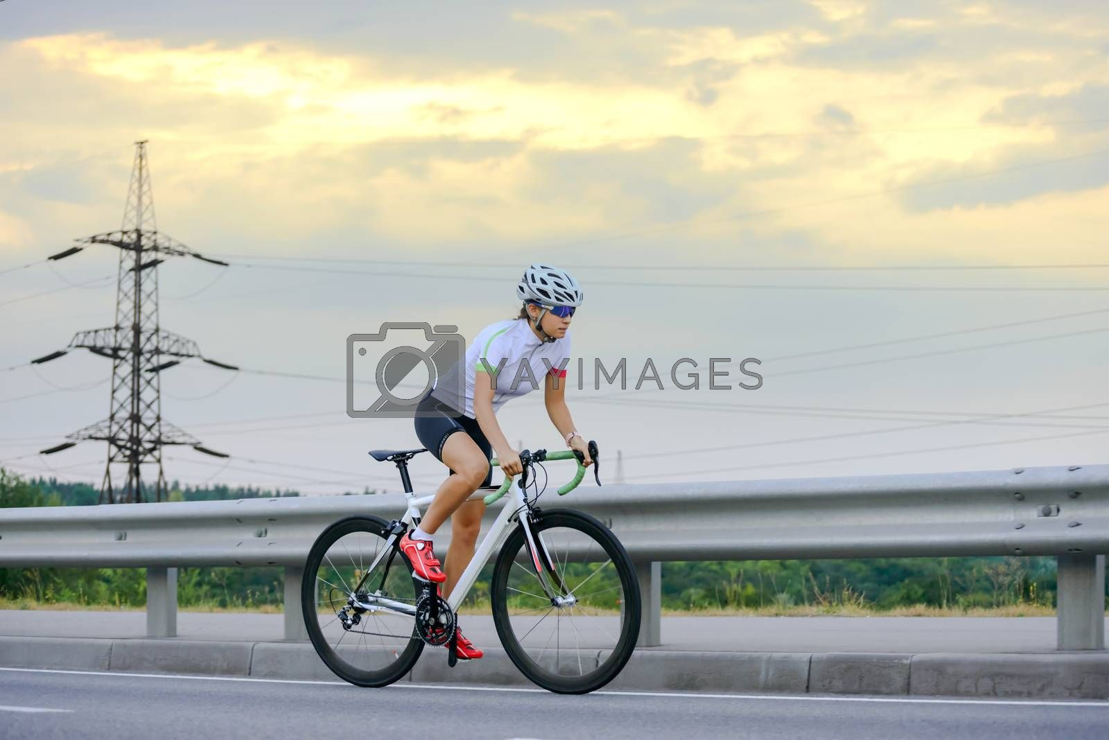 Young Woman Cyclist Riding Road Bike at Sunset. Adventure, Travel, Healthy Lifestyle and Sport Concept.