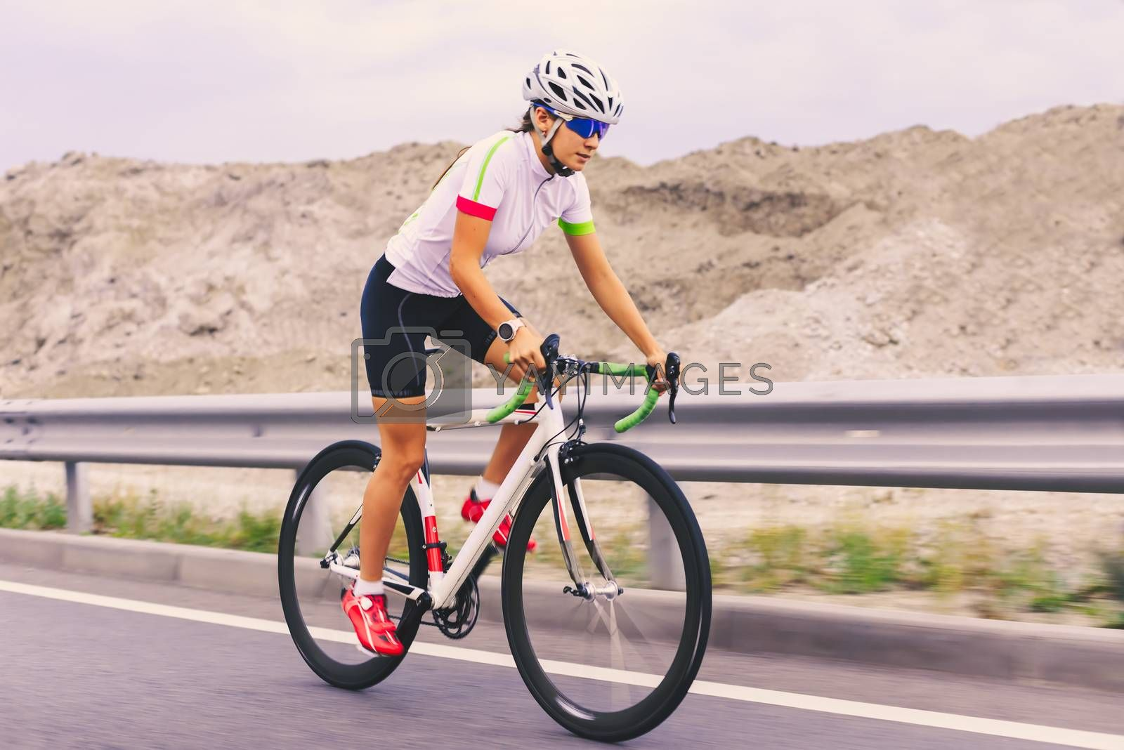 Young Woman Cyclist Riding Bike on the Road in the Mountains. Adventure, Travel, Healthy Lifestyle and Sport Concept.