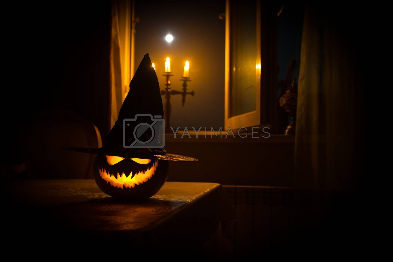 Scary Halloween pumpkin in the mystical house window at night or halloween pumpkin in night on room with blue window. Symbol of halloween in window. by Zeferli