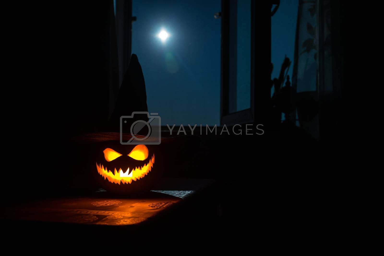 Scary Halloween pumpkin in the mystical house window at night or halloween pumpkin in night on room with blue window. Symbol of halloween in window. by Zeferli