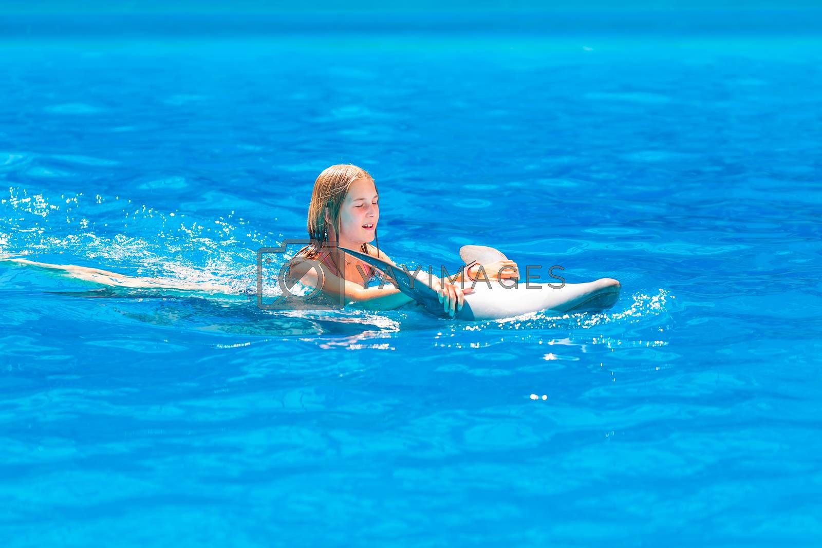 Happy little girl swimming with dolphins in Dolphinarium. Swimming, bathing and communication with dolphins.
