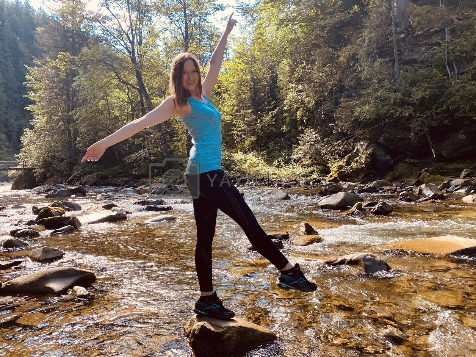 young woman doing yoga exercises on the stone among mountain stream