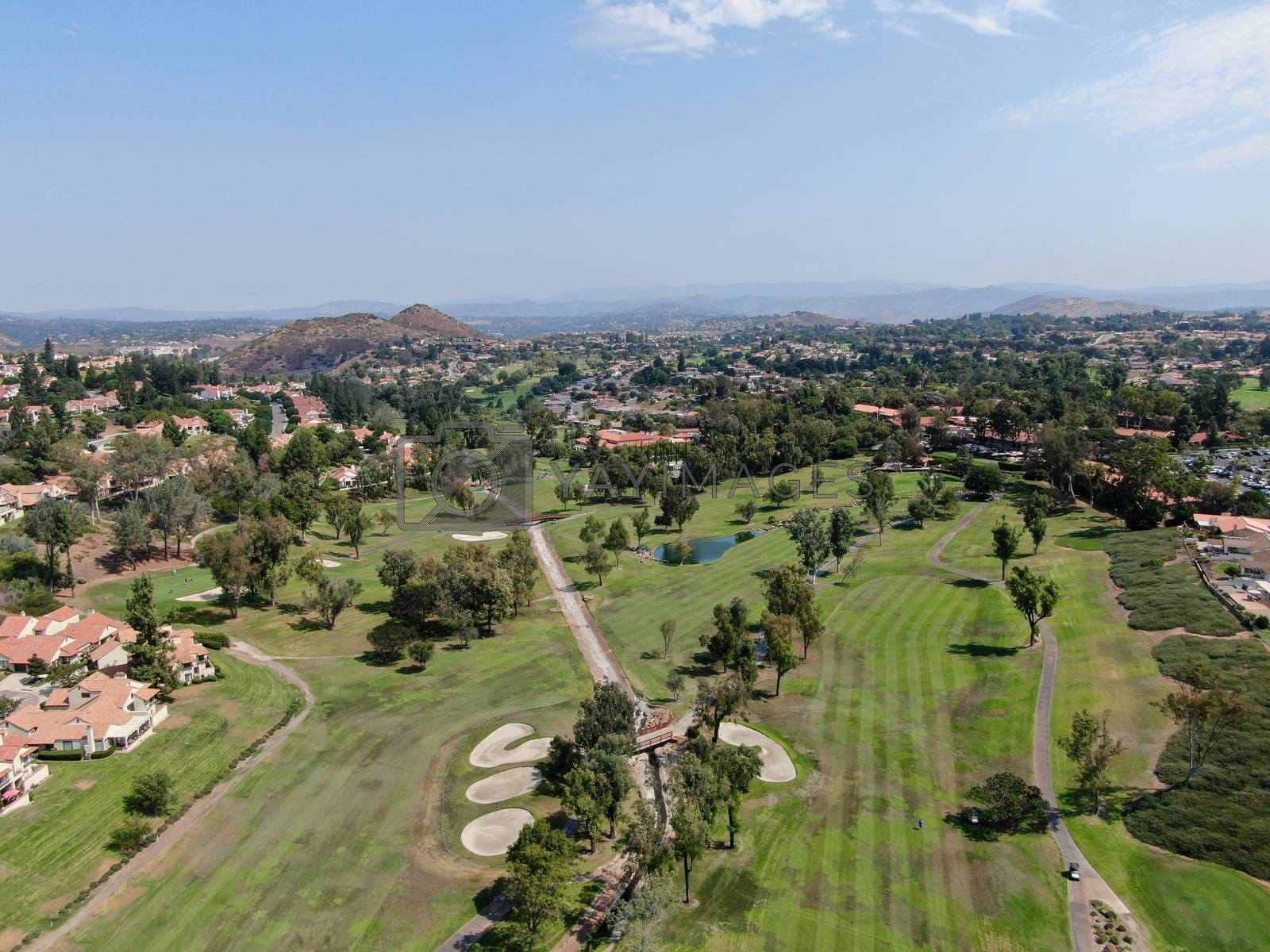 Aerial view of golf in middle class neighborhood surrounded with residential house, and mountain on the background in San Diego, South California, USA.