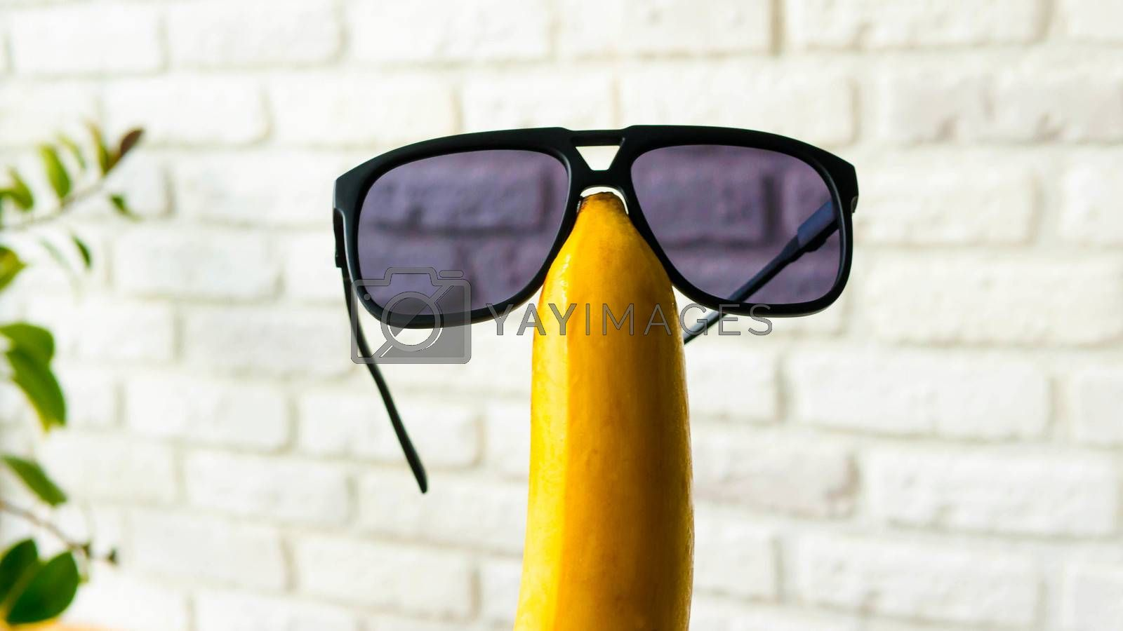 Royalty free image of Sunglasses on a banana on a brick wall background,close-up.Cheerful fruit with glasses by Andriii_Klapkoo