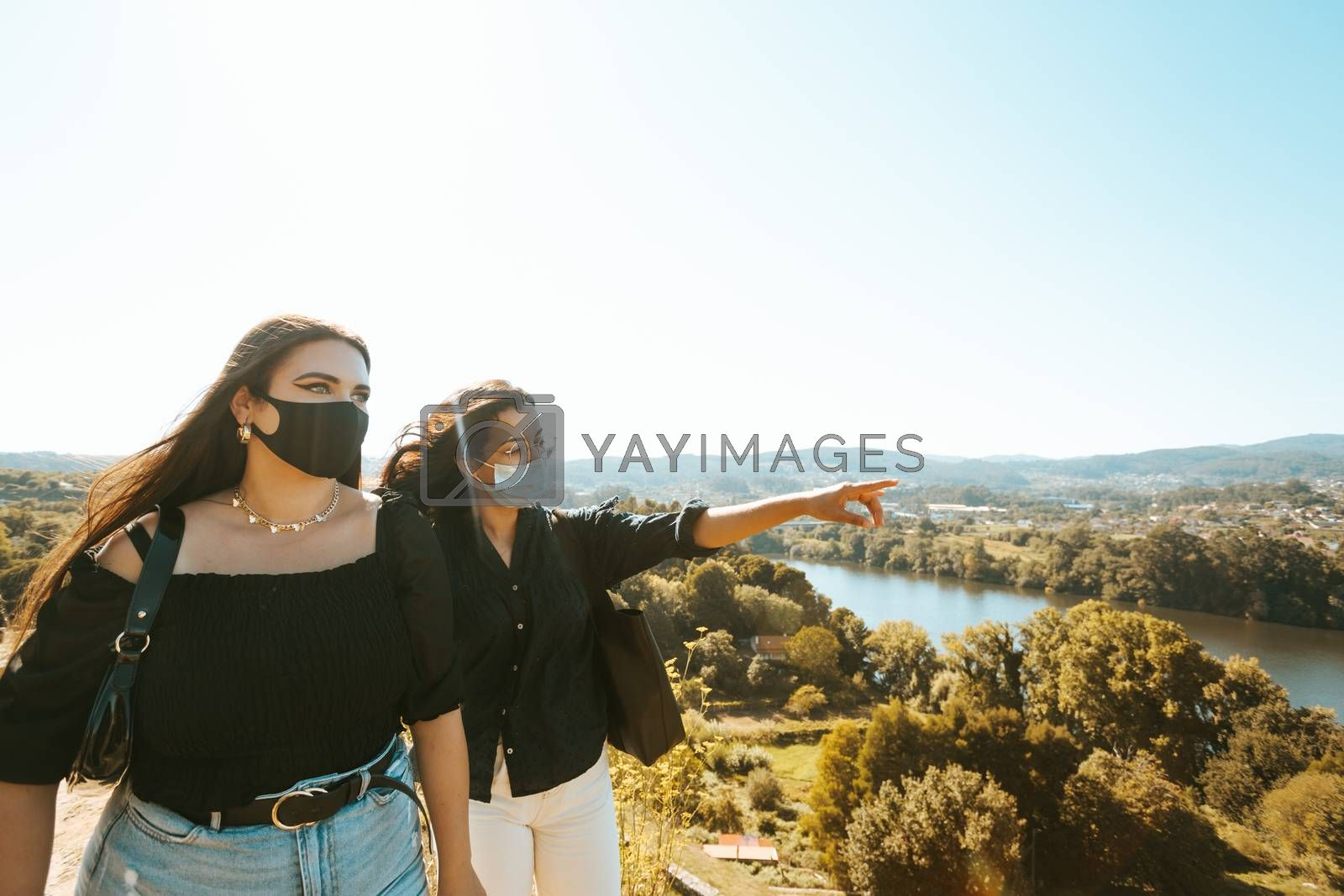 One woman explains another woman the landscape while they both use masks on a sunny day