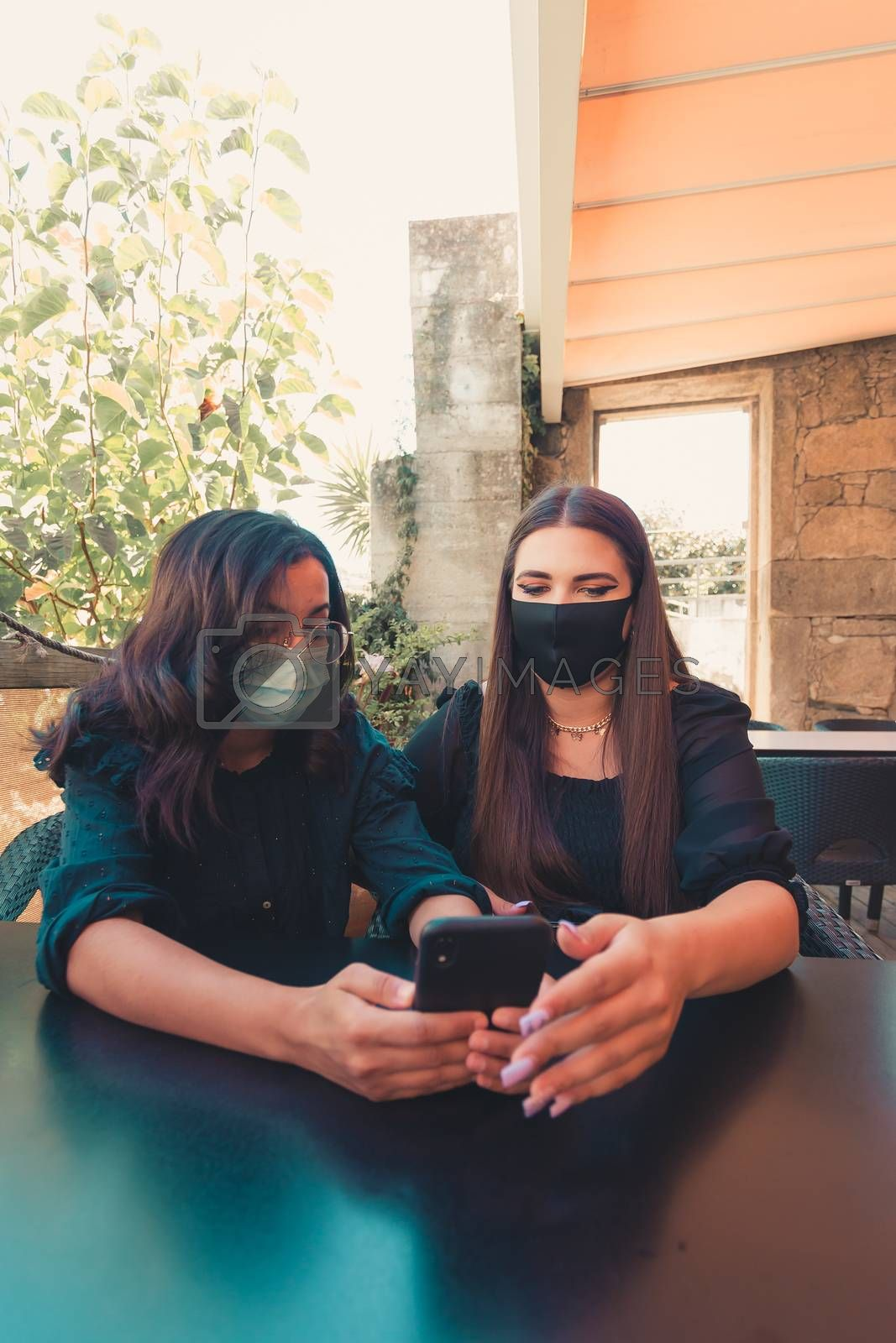 A vertical shot of two women using masks looking at the screen of the phone in a bar