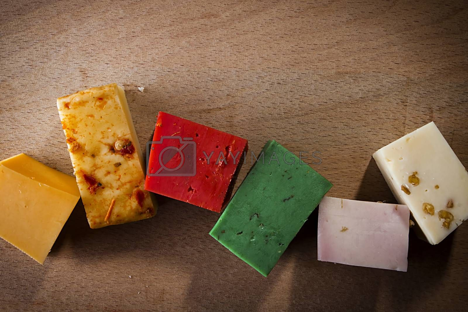 Pieces of colorful cheeses on a wooden background