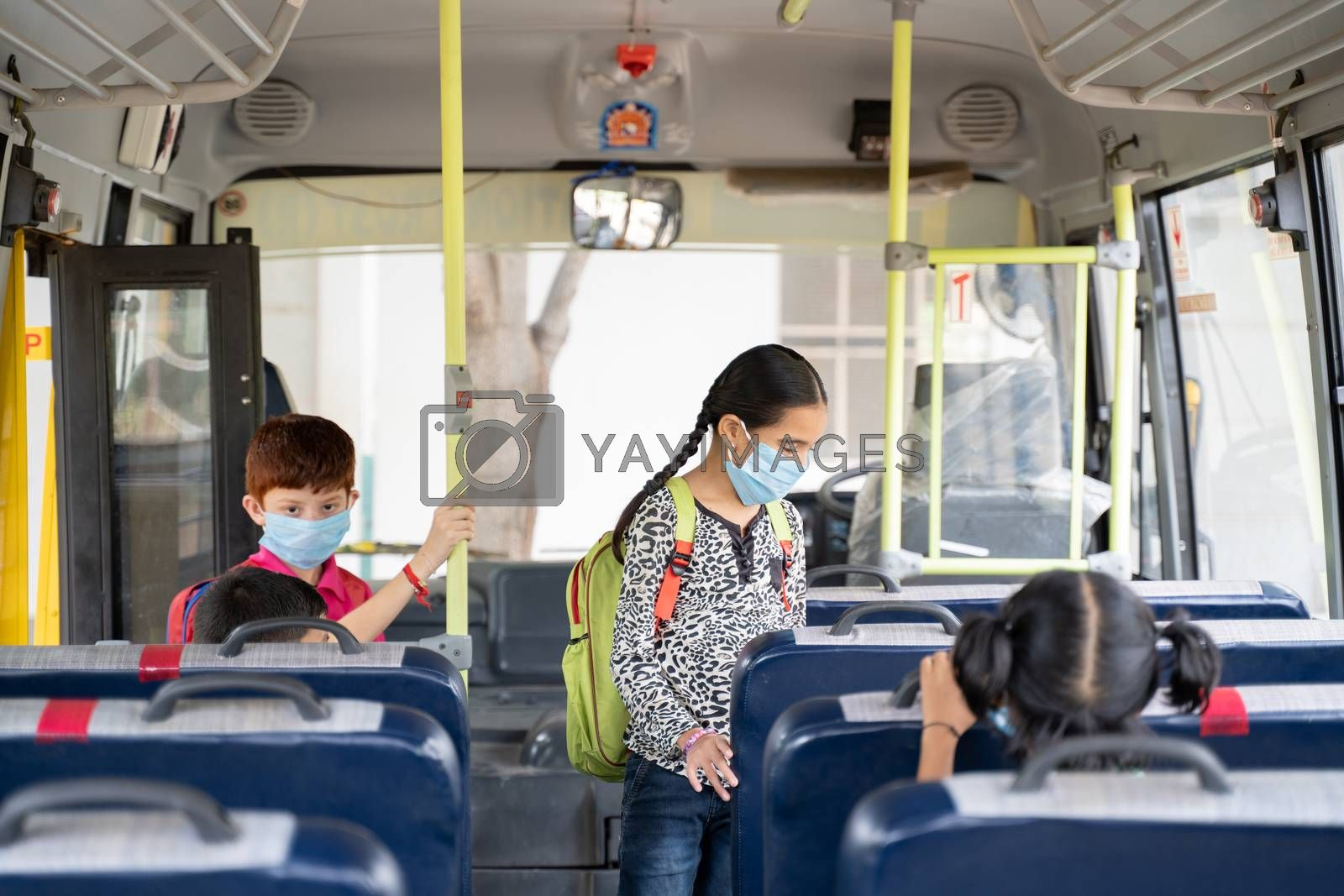 Kids with medical mask coming inside school bus and sitting on seats while maintaining social distance due to coronavirus or covid-19 pandemic - Concept of school reopen or back to school.