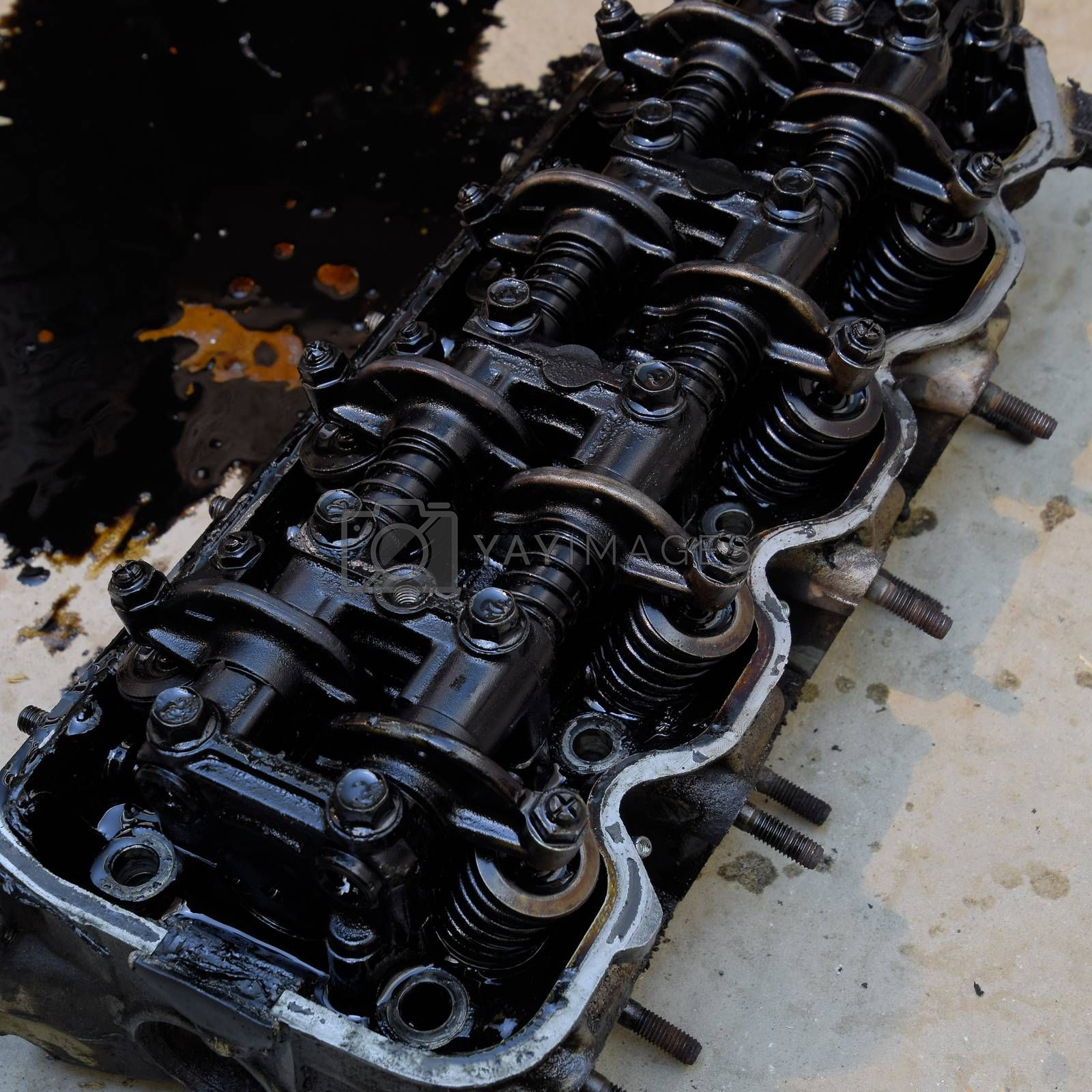 The head of the block of cylinders. The head of the block of cylinders removed from the engine for repair. Parts in engine oil. Car engine repair in the service.
