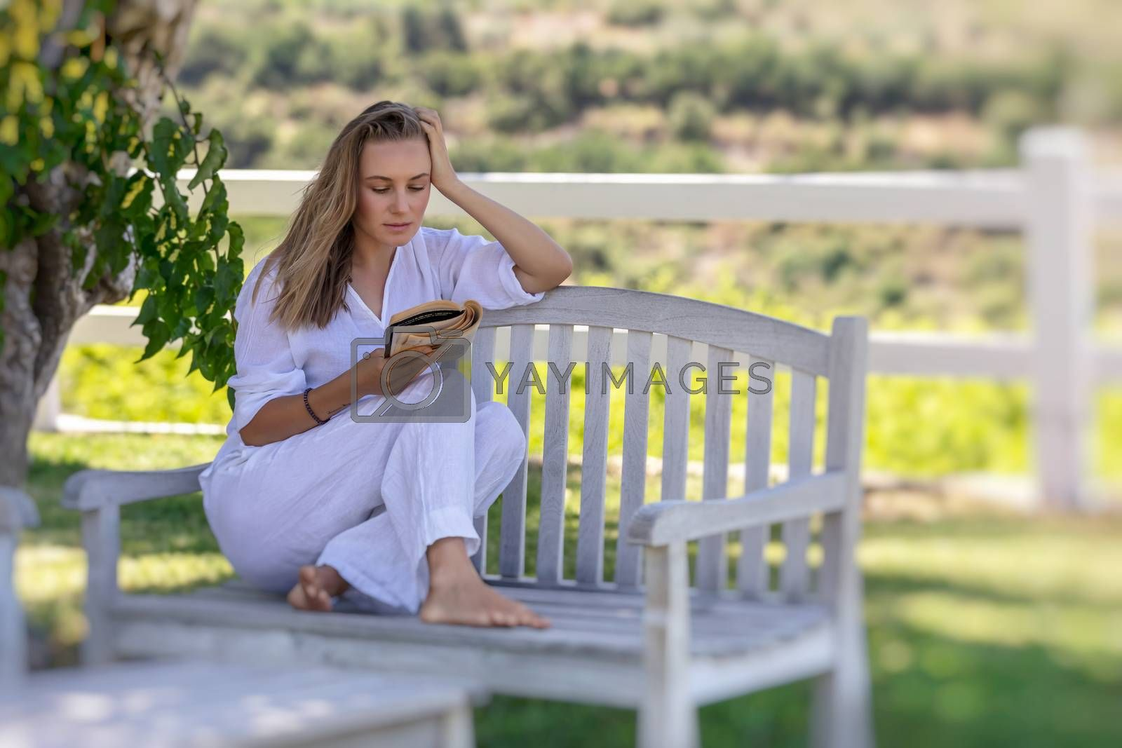 Beautiful Girl Reading Book Outdoors. Nice Female Spending Leisure Time in Countryside Ranch. Perfect Place to Enjoying Calm Summer Vacation.