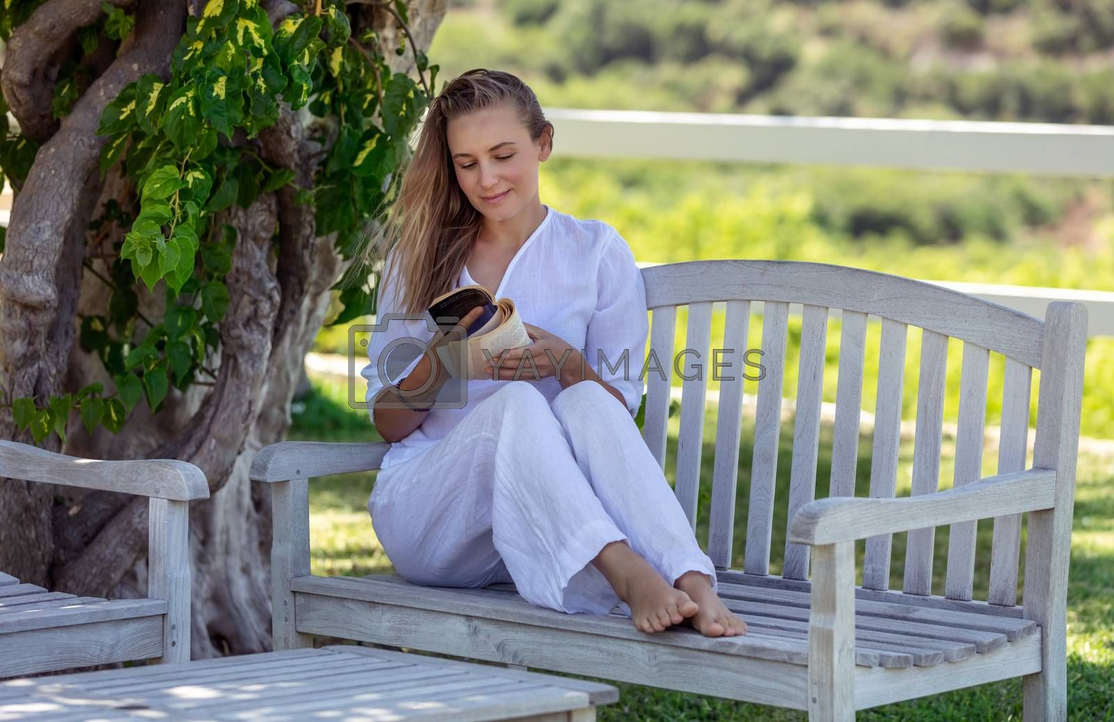 Beautiful Young Woman Sits on the Bench in the Park and Reading a Book. Spending Nice Summer Day with Good Novel in Nature. Peace and Relaxation Concept.