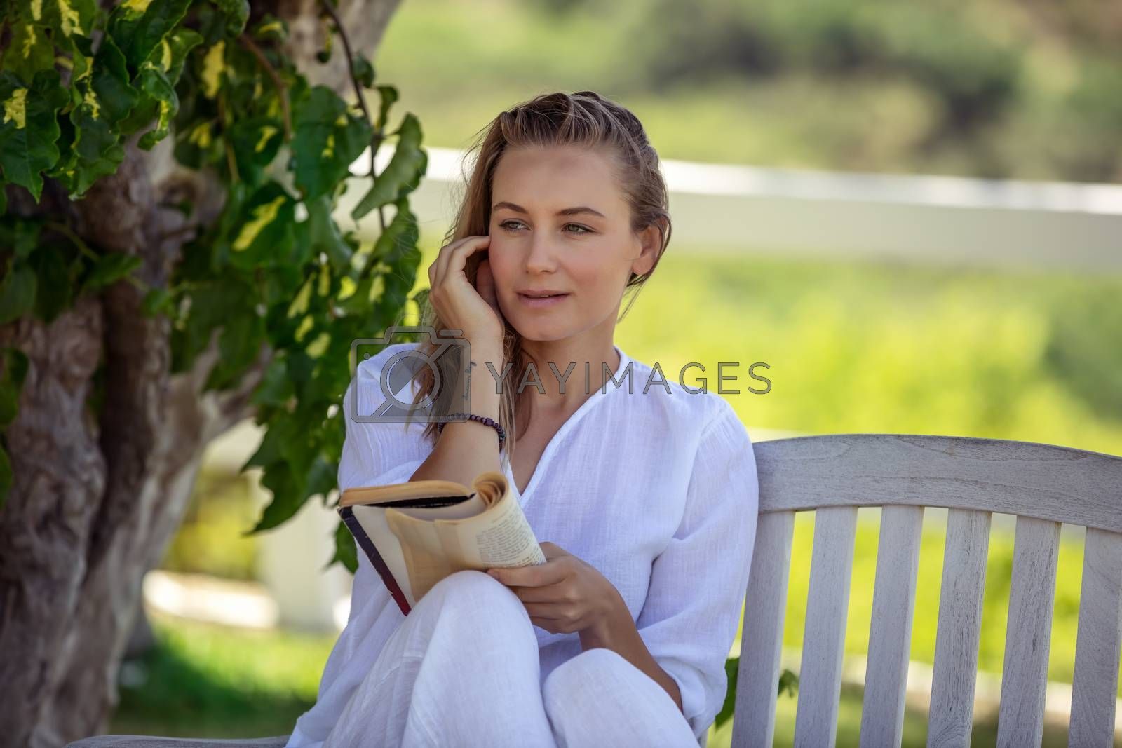Portrait of a Pretty Female in the Summer Park Sits on the Bench and with Pleasure Reading a Book. Enjoying Interesting Story. Education Outdoors. Leisure Time.