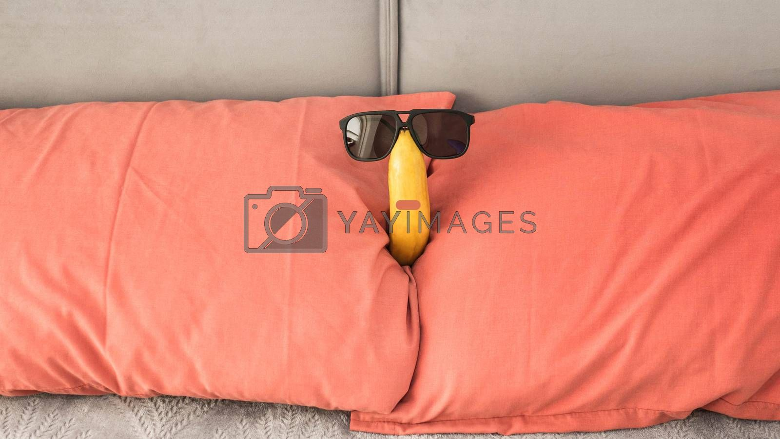 Royalty free image of A funny banana in sunglasses lies on the bed in the hotel,close-up. by Andriii_Klapkoo