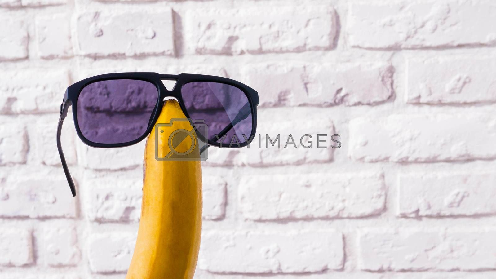 Royalty free image of Banana in sunglasses on a brick wall background,close-up. by Andriii_Klapkoo