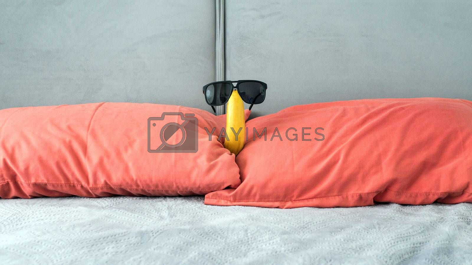 Royalty free image of Banana with glasses in the apartment on the bed in the bedroom, red pillows,funny banana with glasses. by Andriii_Klapkoo
