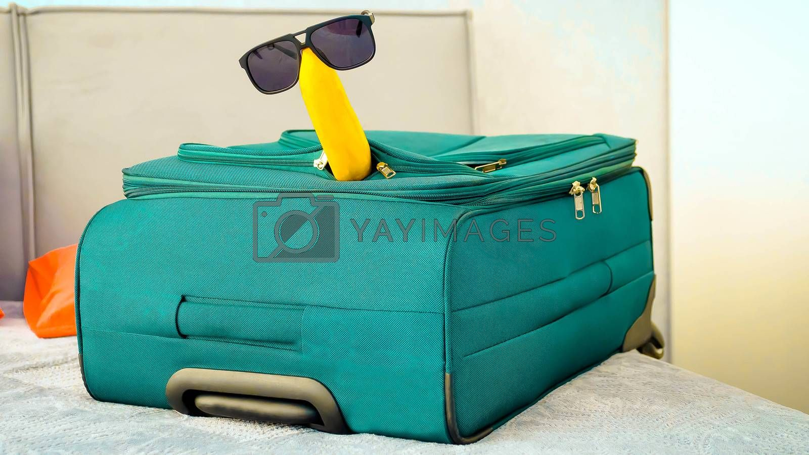 Royalty free image of Banana in sunglasses with a suitcase in an apartment,in a hotel on the bed,close-up. by Andriii_Klapkoo