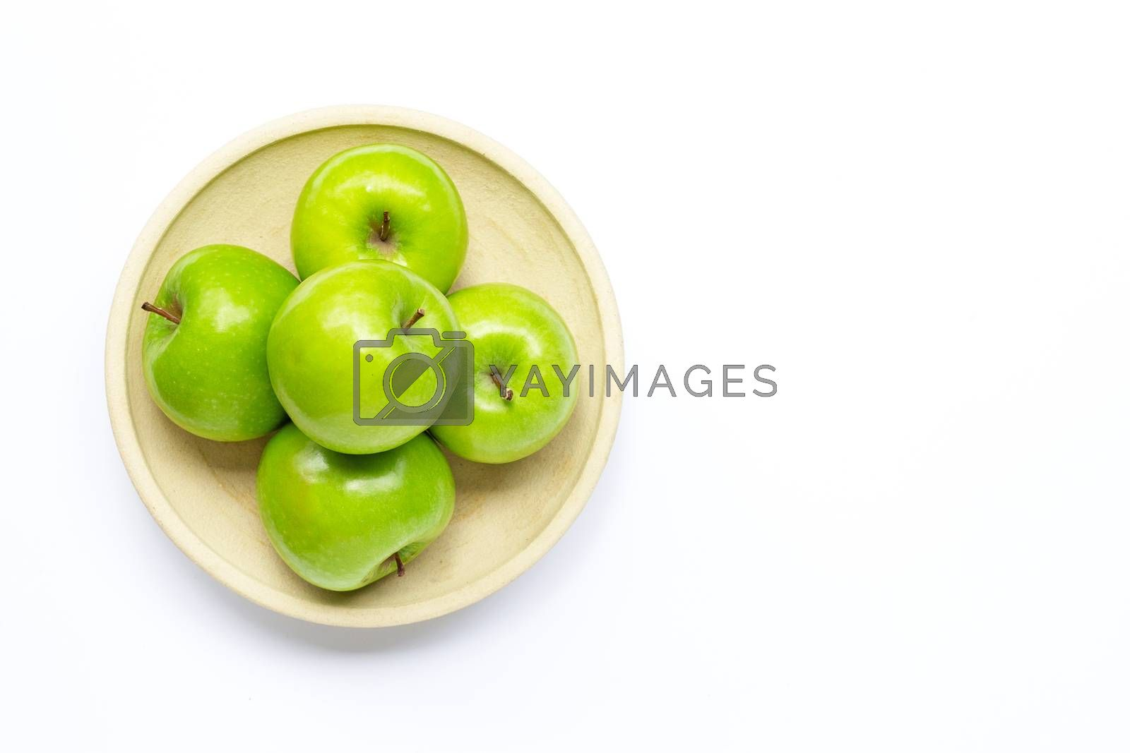 Fresh green apples on pottery plate on white background. Copy space
