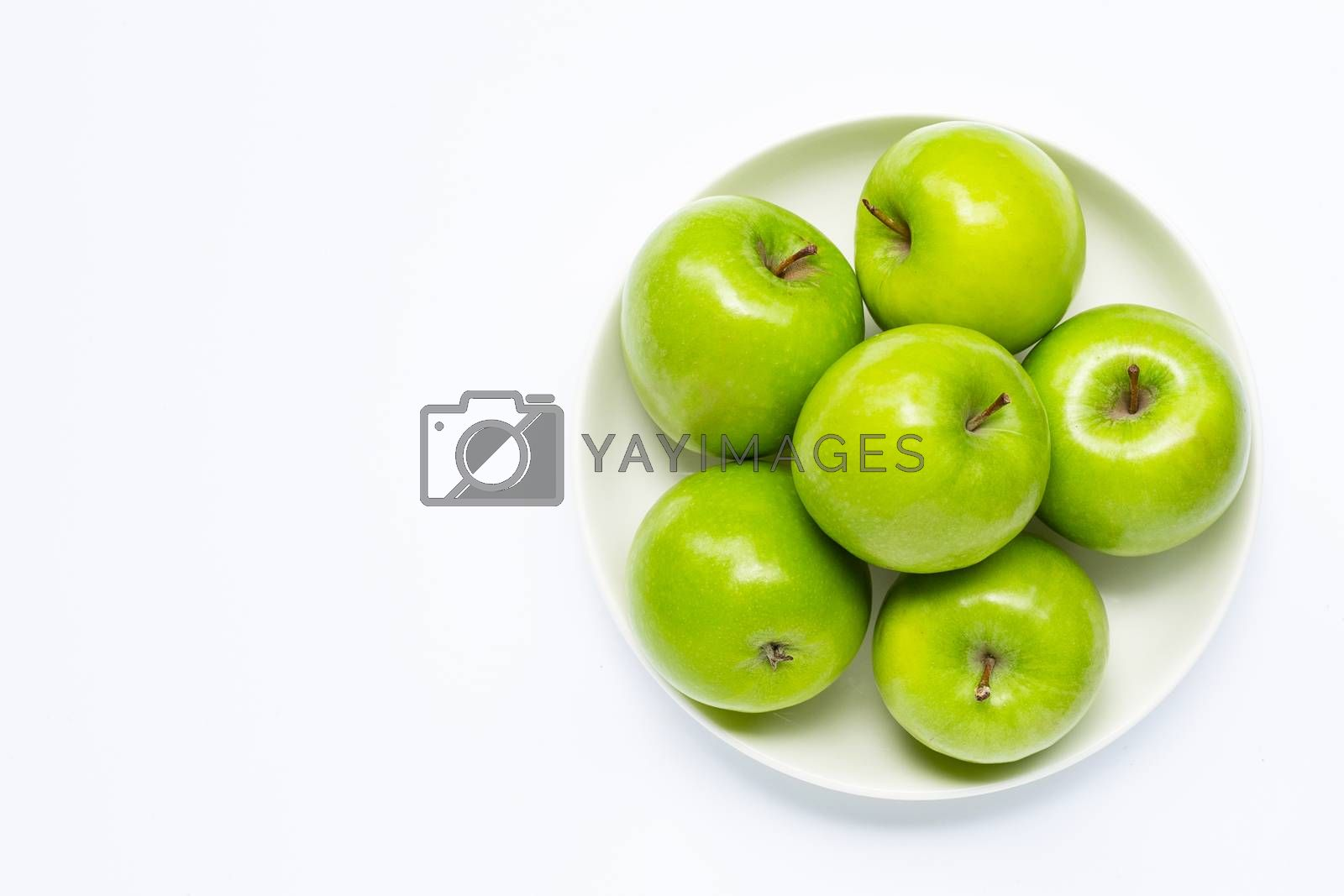 Fresh green apples on  white plate on white background. Copy space