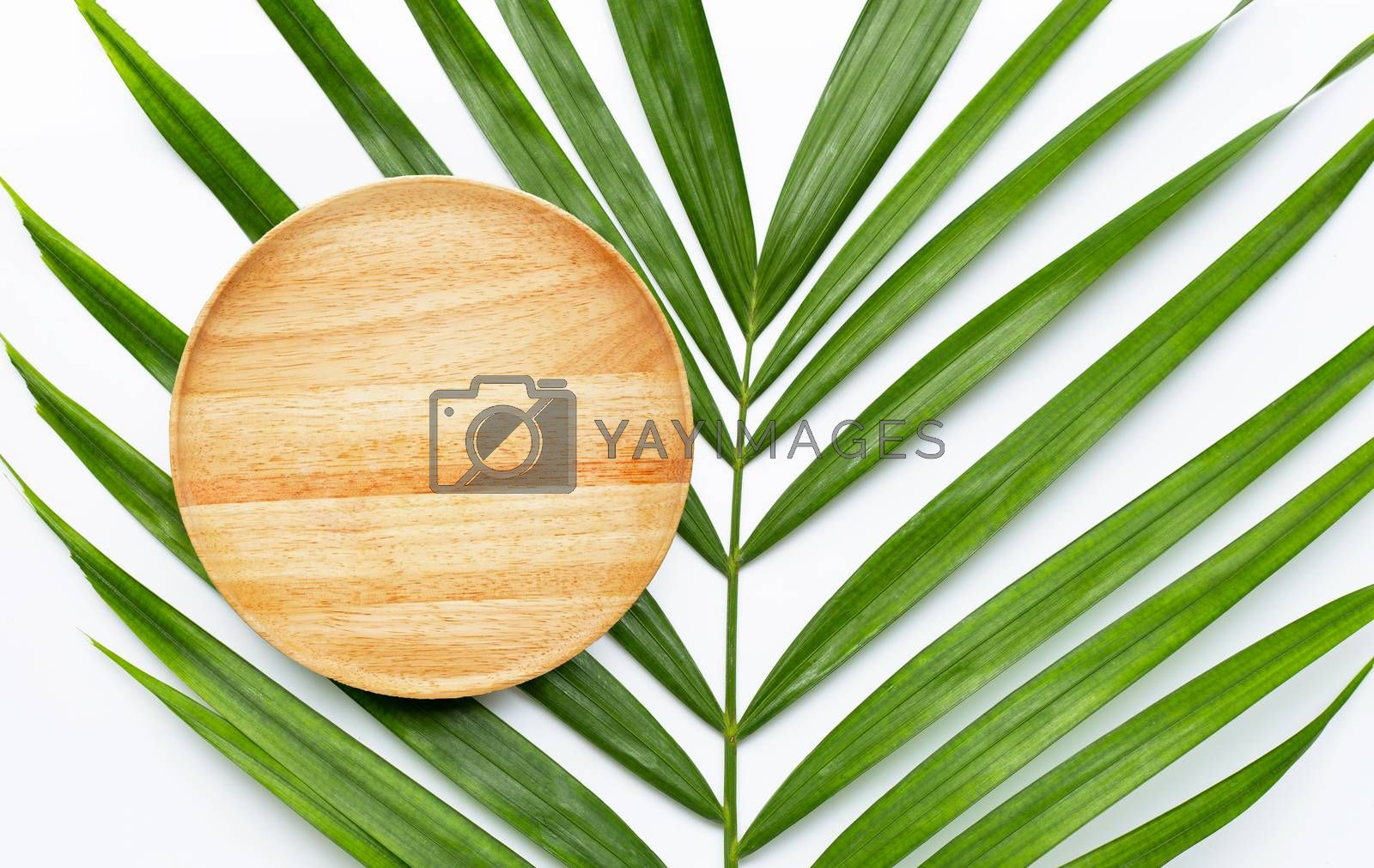 Empty wooden plate on tropical palm leaves on white background. Top view