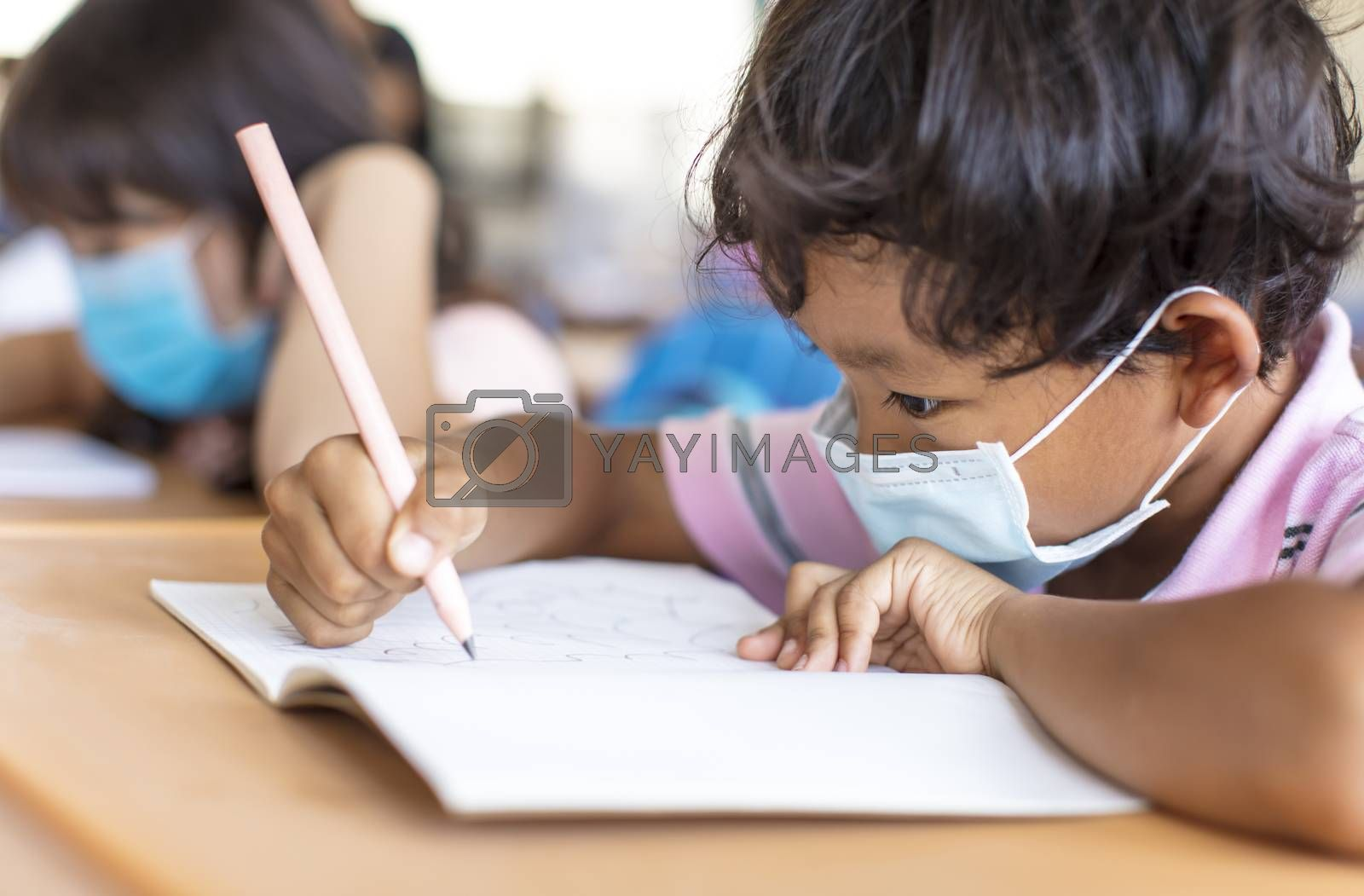 school boy wearing  mask and study in classroom