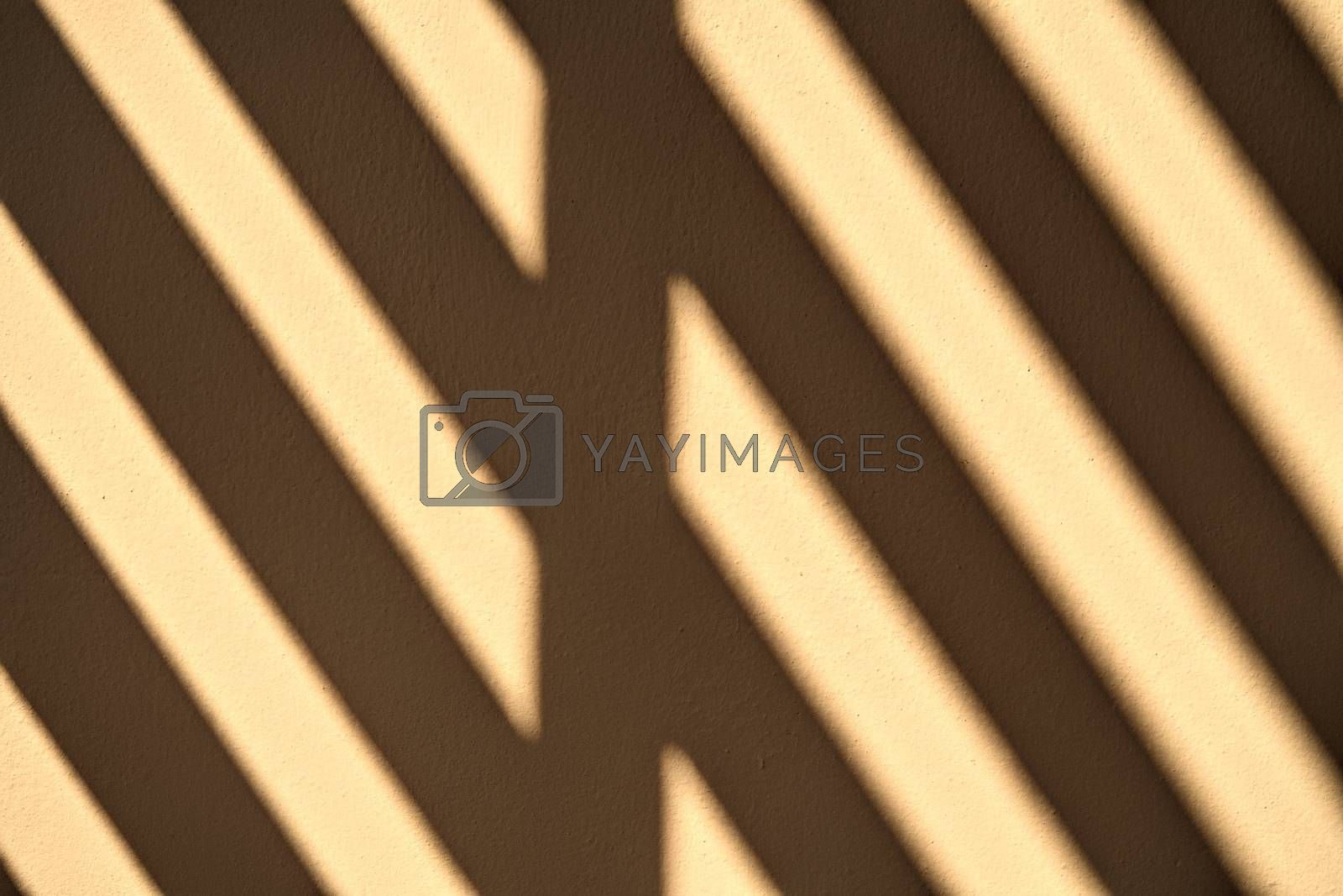 Abstract sunlight shines through the wooden channel against the cement wall.