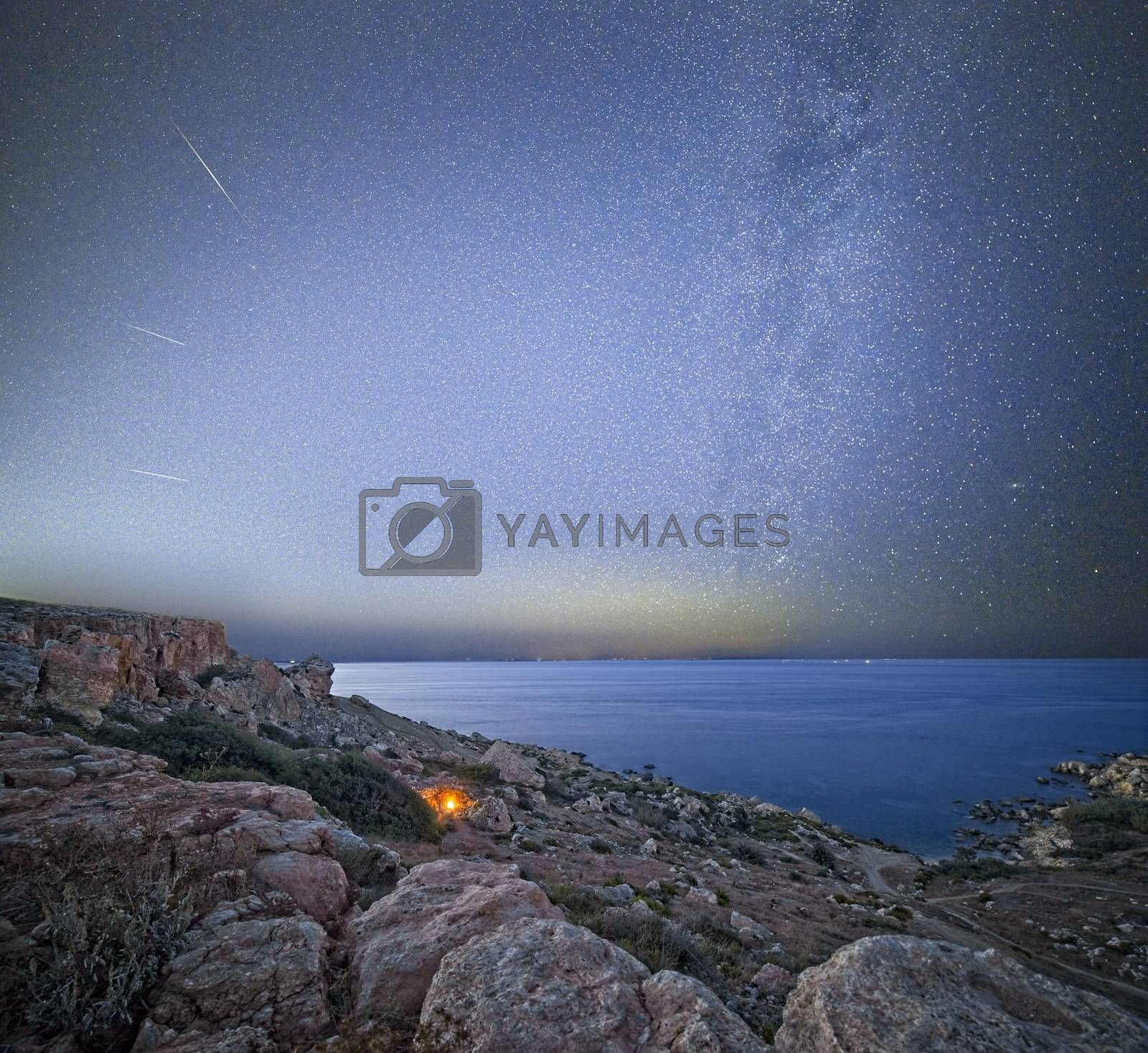 A campfire burns below the cliffs of Selmun, while three Perseid meteors radiate away from the Milky Way, which in turn seemingly rises up from the glare caused by the distant specks of light on the Sicilian coast.