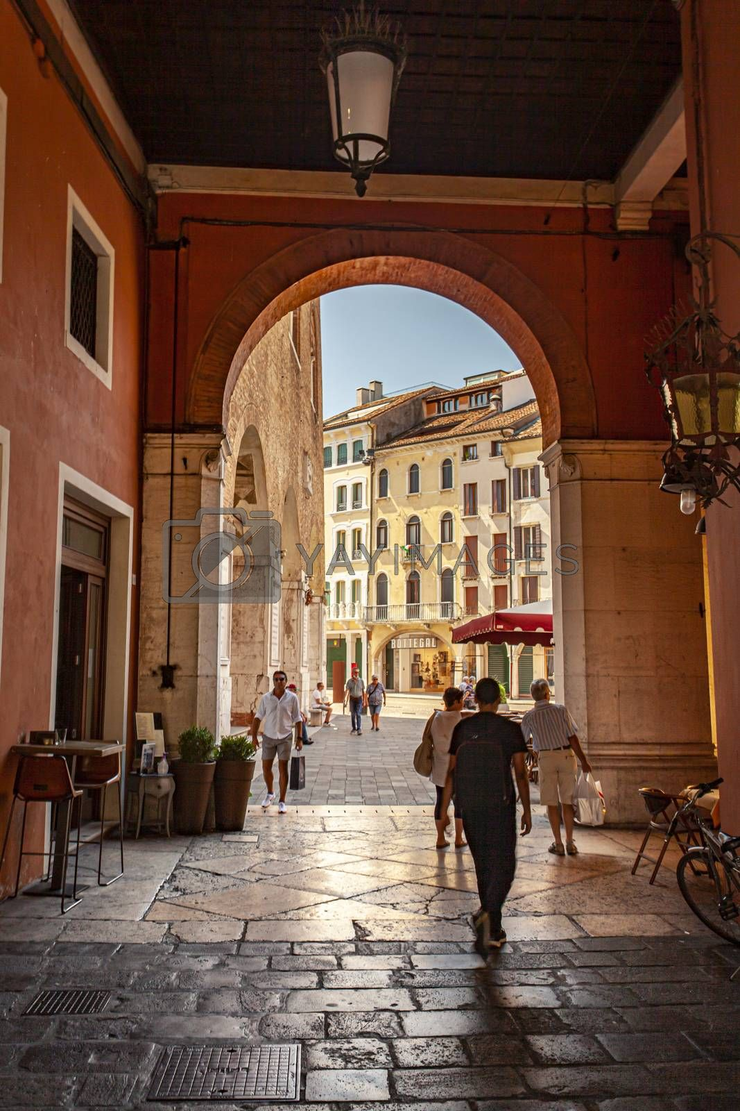 TREVISO, ITALY 13 AUGUST 2020: Arcades in Piazza dei signori in Treviso with people passing through