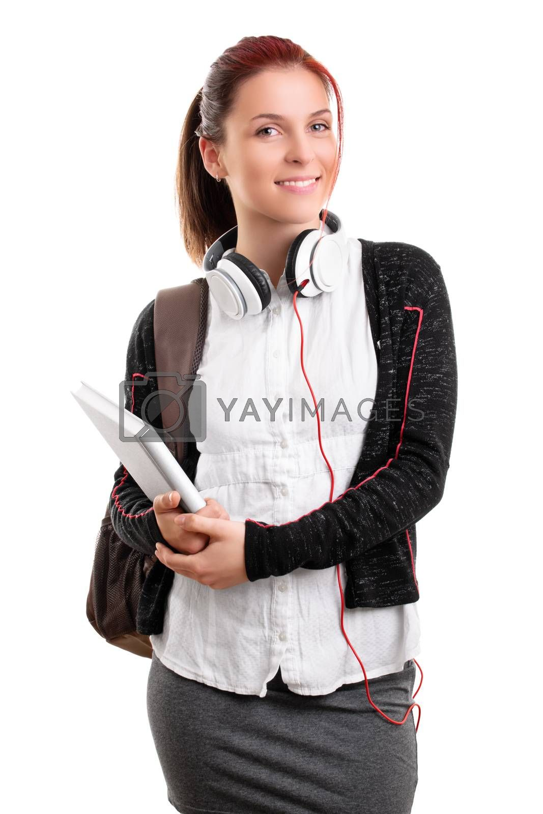 Beautiful smiling young girl in schoolgirl uniform with backpack and headphones, holding a notebook, isolated on white background. Student ready for class. Education concept.