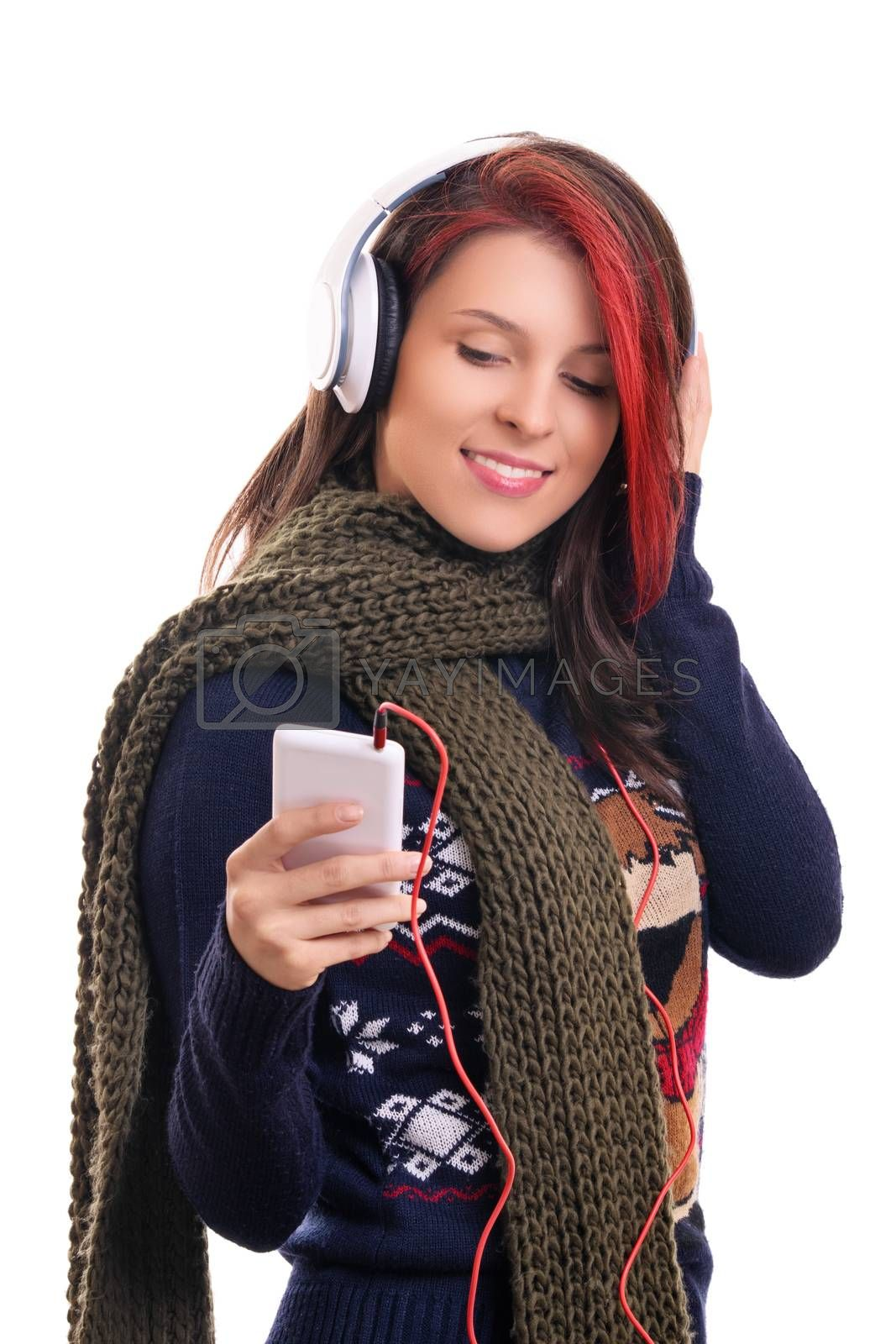 Beautiful smiling young woman wearing winter scarf with headphones listening to music, looking at her mobile phone, isolated on white background. Season, technology and people concept.