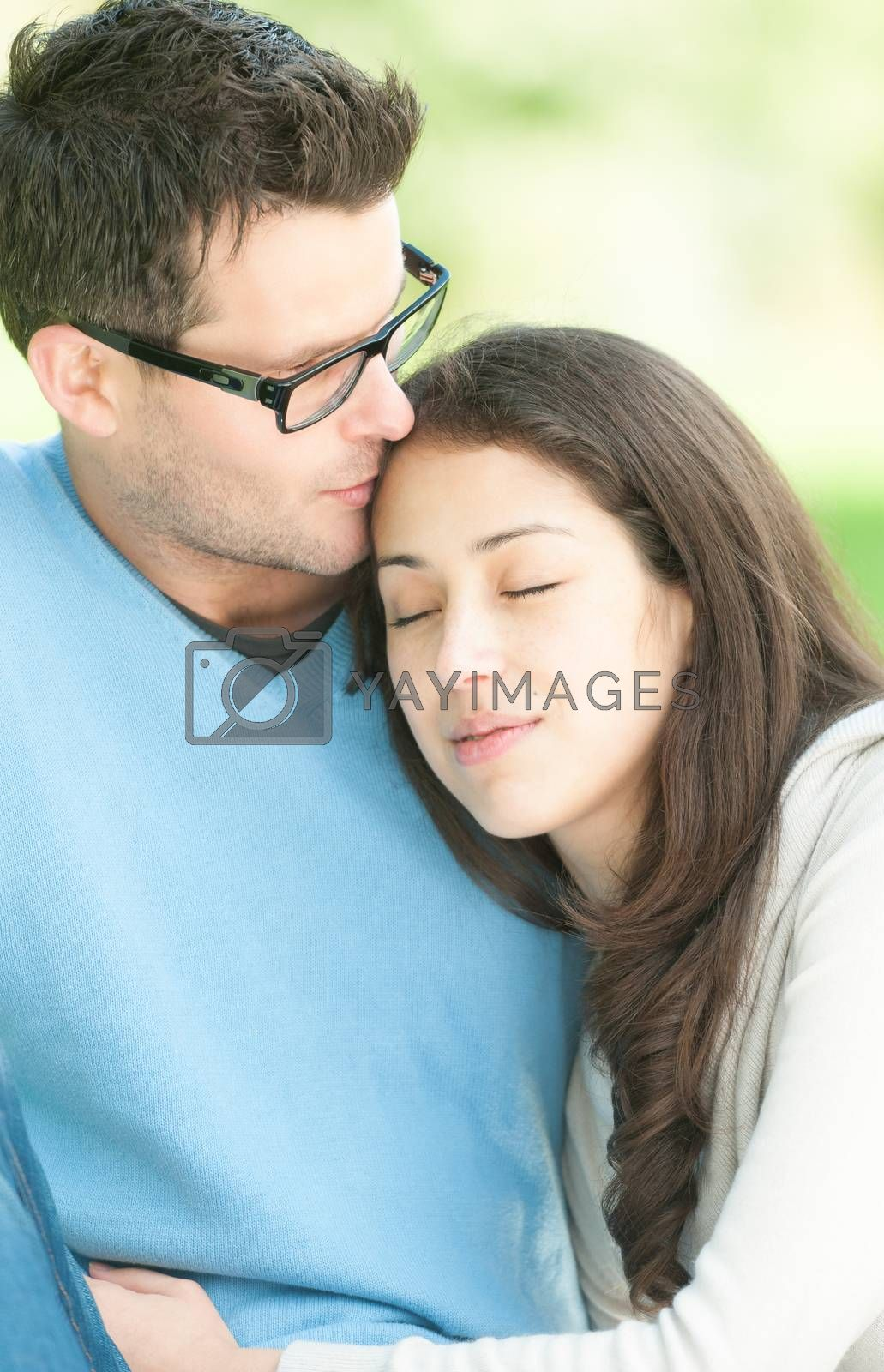 Portrait of young sweet couple spending time outdoor together. Woman leaning on man's shoulder with her eyes closed. Quiet and peaceful atmosphere. Romantic relationships. Family and love.