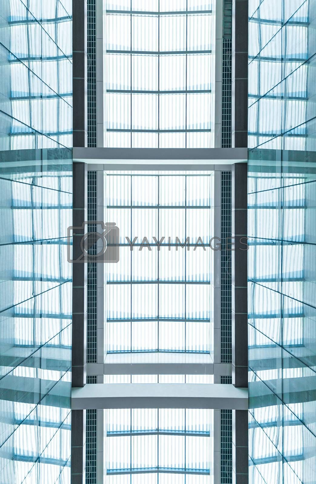 View through modern skylight of blue glass. Roof of building with square symmetric sections. Contemporary architectural style. Abstract backgrounds and backdrops.