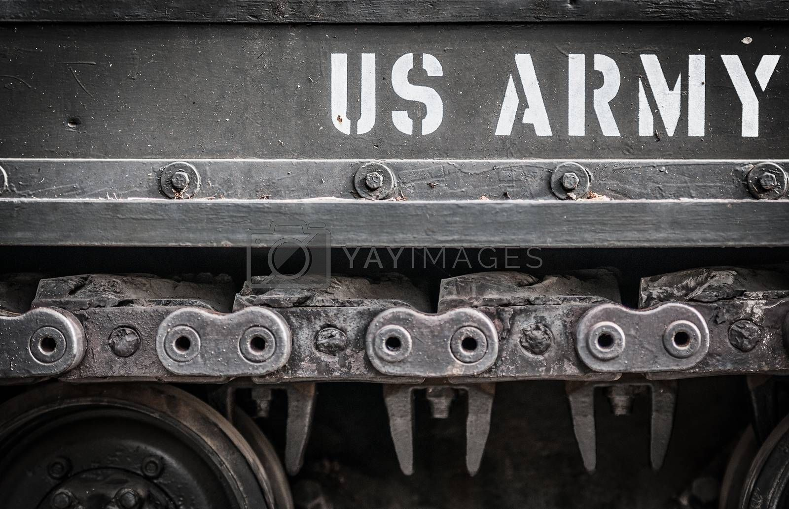 Tank close-up with wheel, caterpillar and text US Army on it. Focus on side of military transport with white letters outdoors. Armored machine of America. American tank.