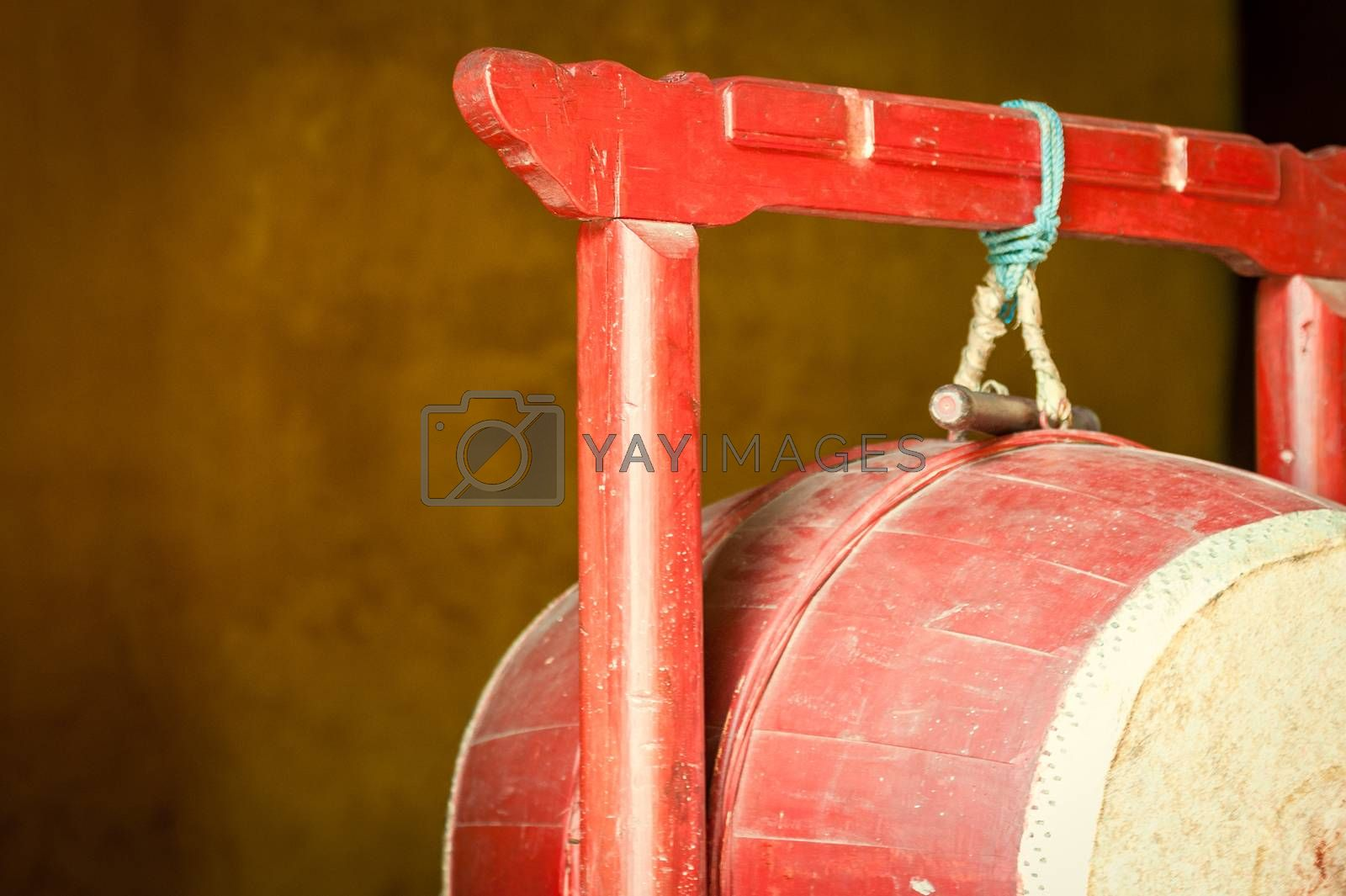 Detail of red drum hanging on red wooden rack in Buddhist temple. Religious attributes used in ceremony. Religion and traditions of East. Symbol of Asian faith and culture.