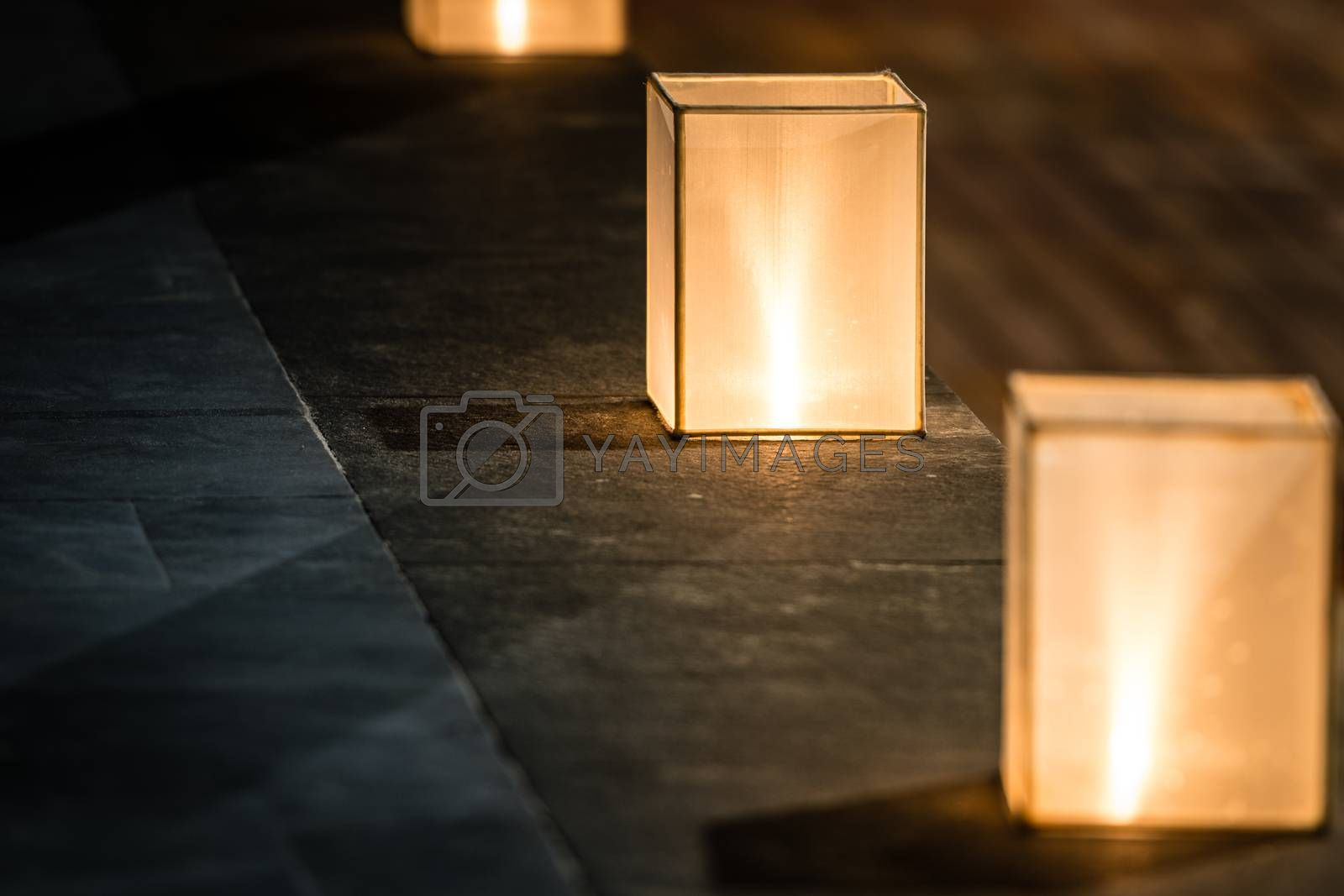 Row of three square lanterns with dim light standing on stone floor. Focus on central lantern. Street decoration and lighting. Warm and romantic atmosphere of evening.