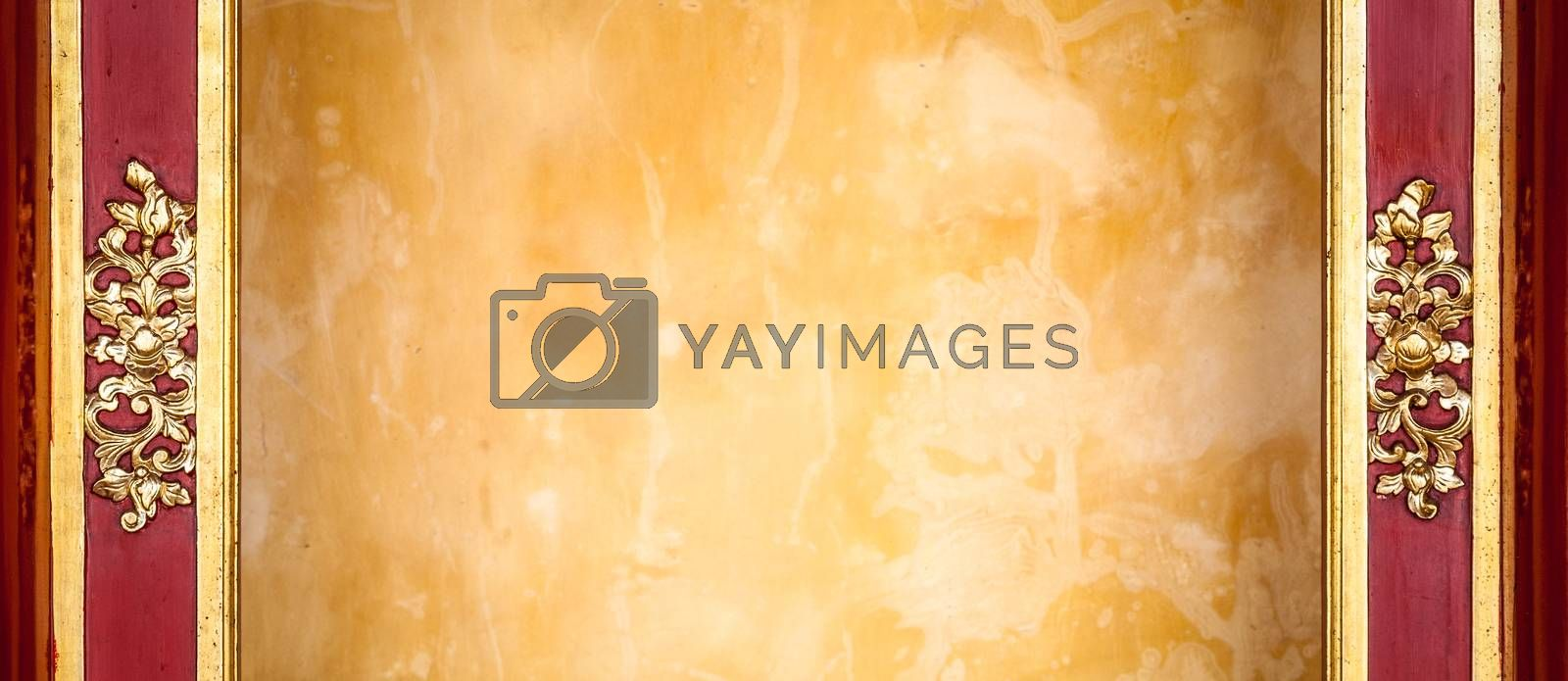 Wall with yellow stucco framed with decoration. Grungy wall with golden floral pattern on dark brown wooden boards both sides. Abstract background. Building exterior or interior.