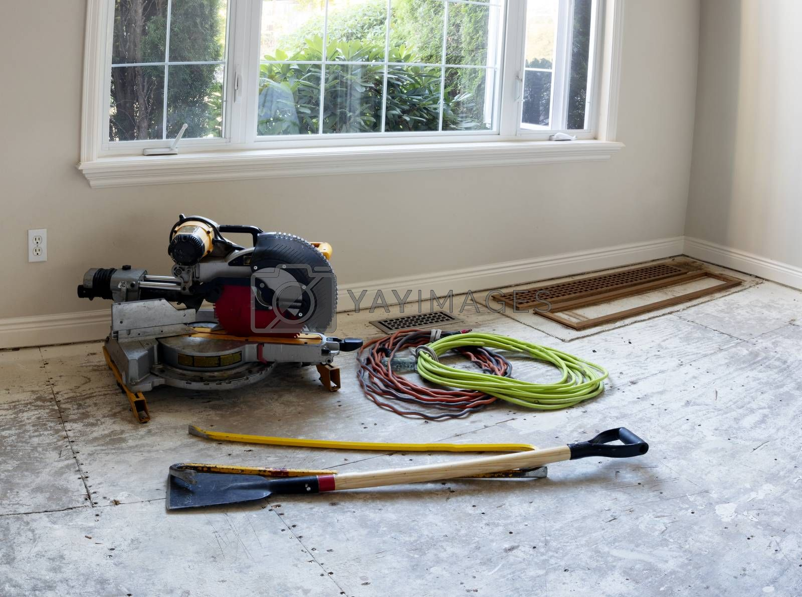 Floor stripped down to plywood with construction tools being prepared for new wood installation