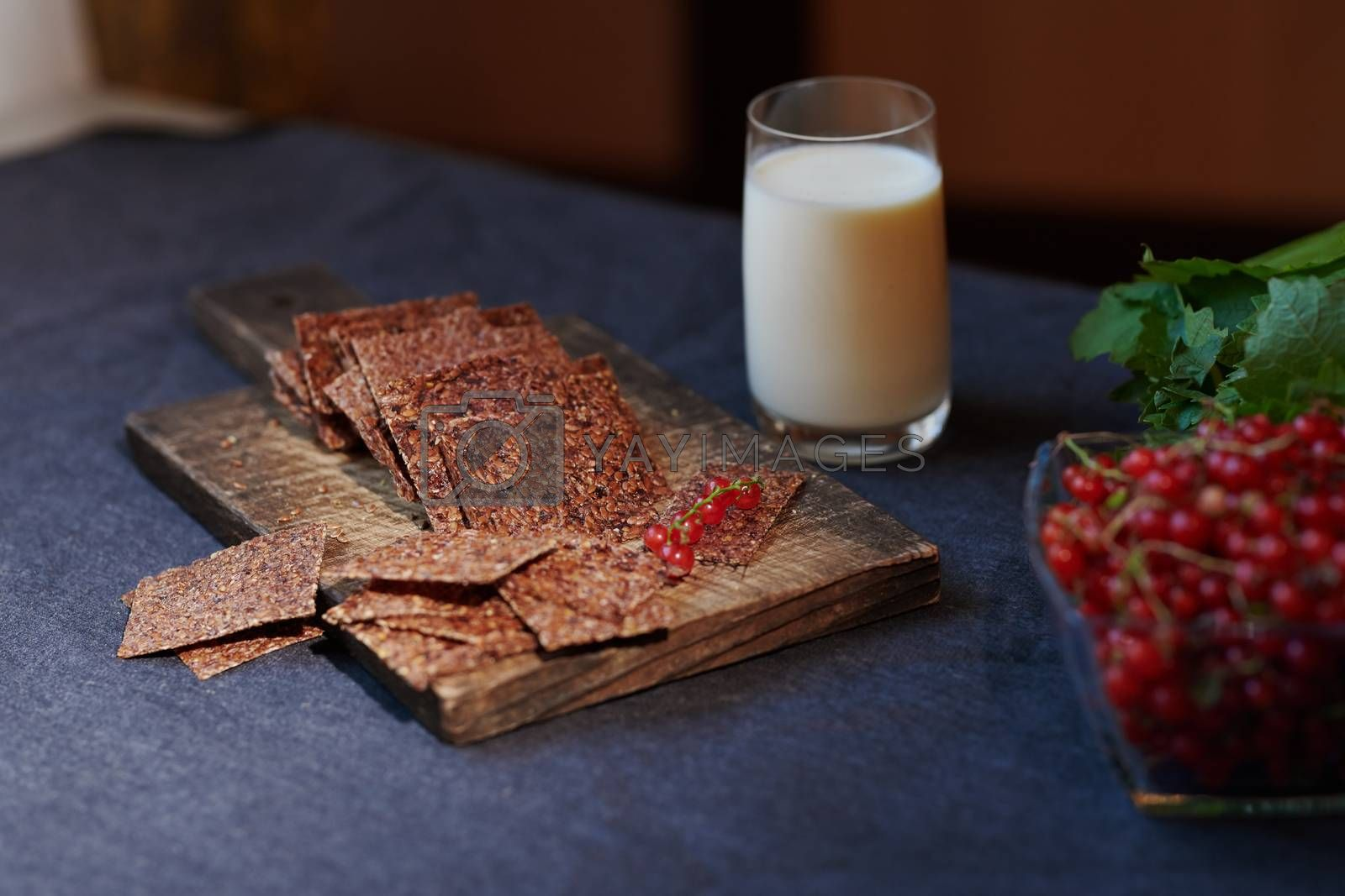 Vegan flaxseed bread with berries next to the glass with coconut milk
