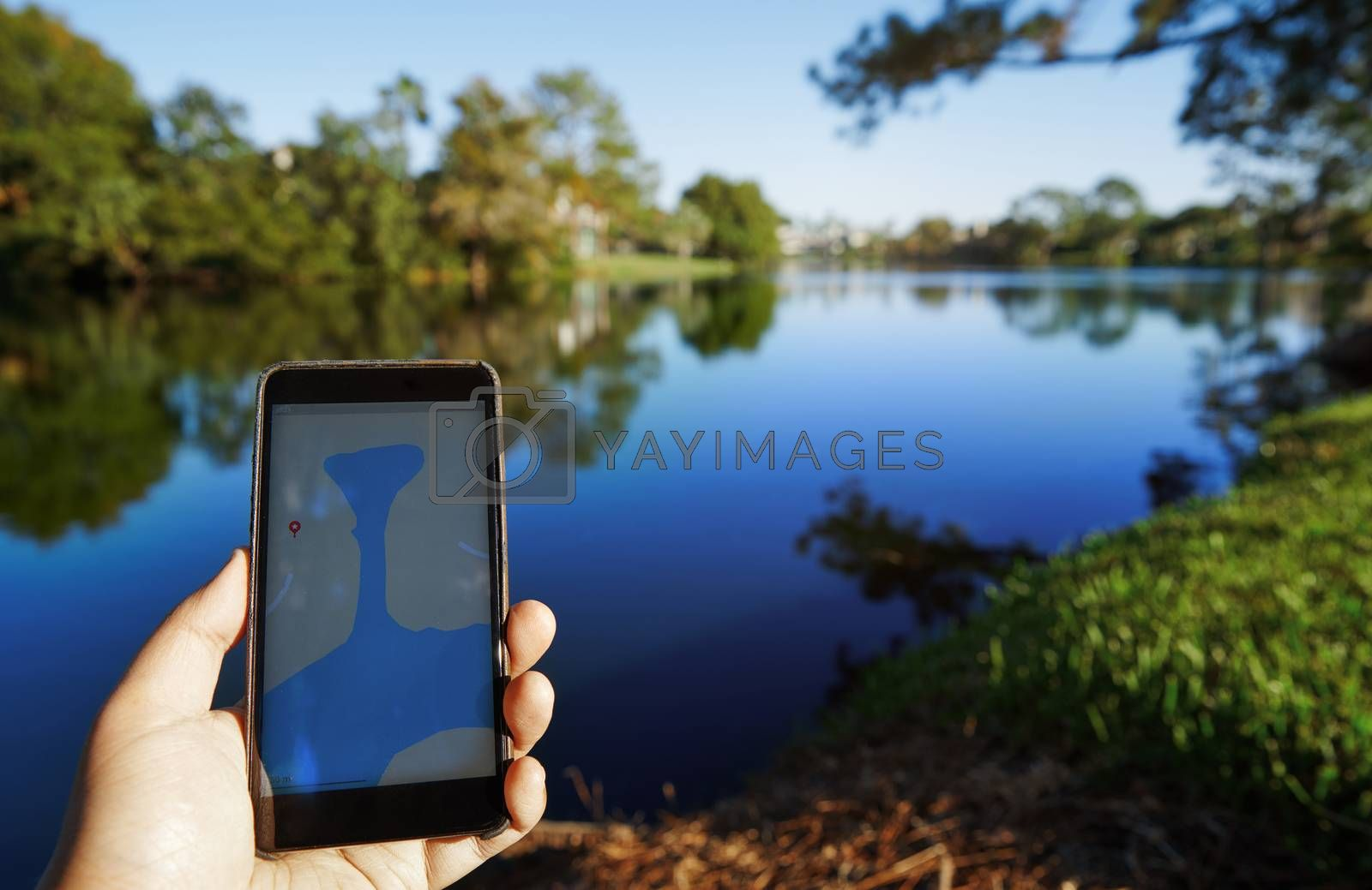 Man using mobile map app next to the lake