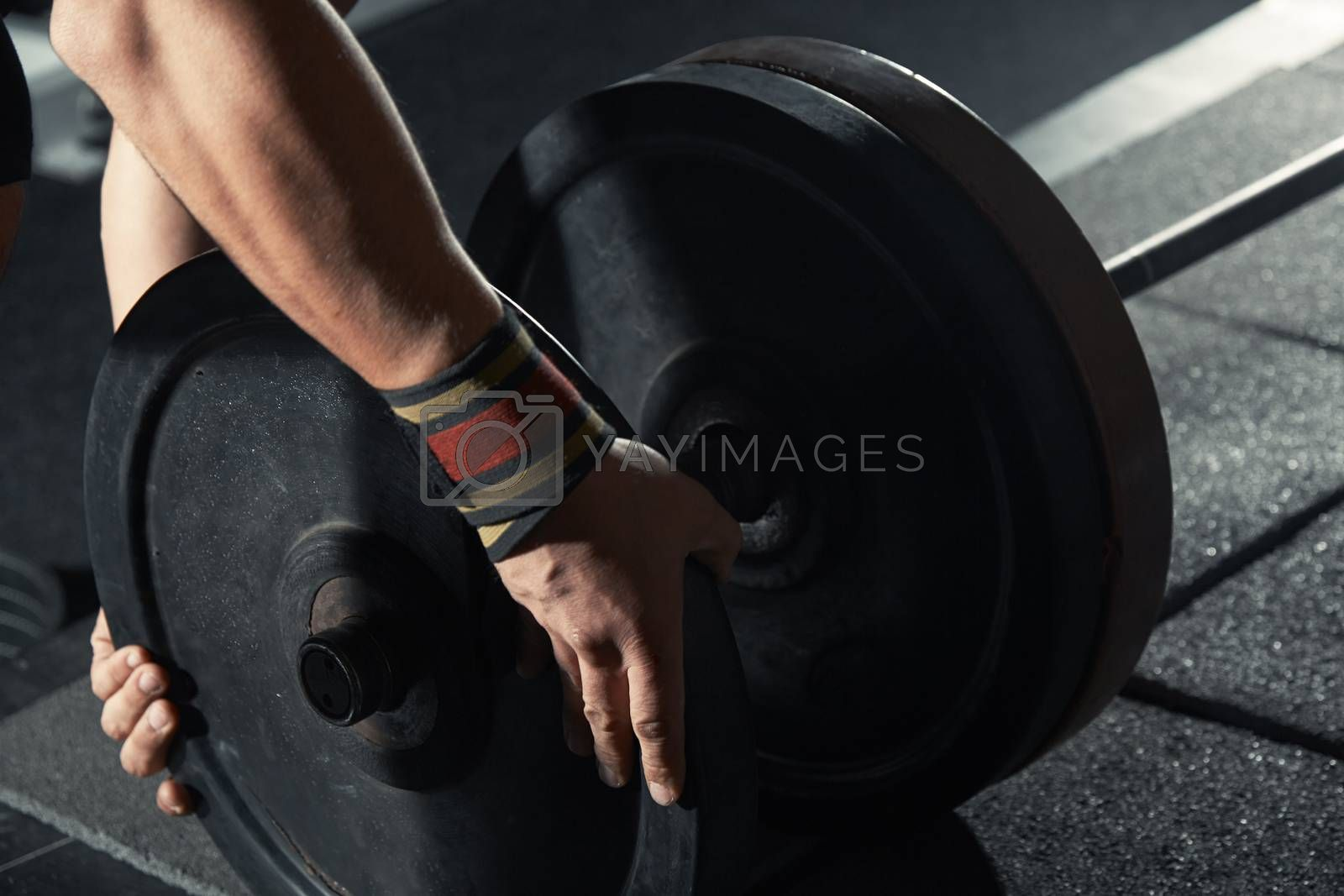 Man preparing barbell at fitness club