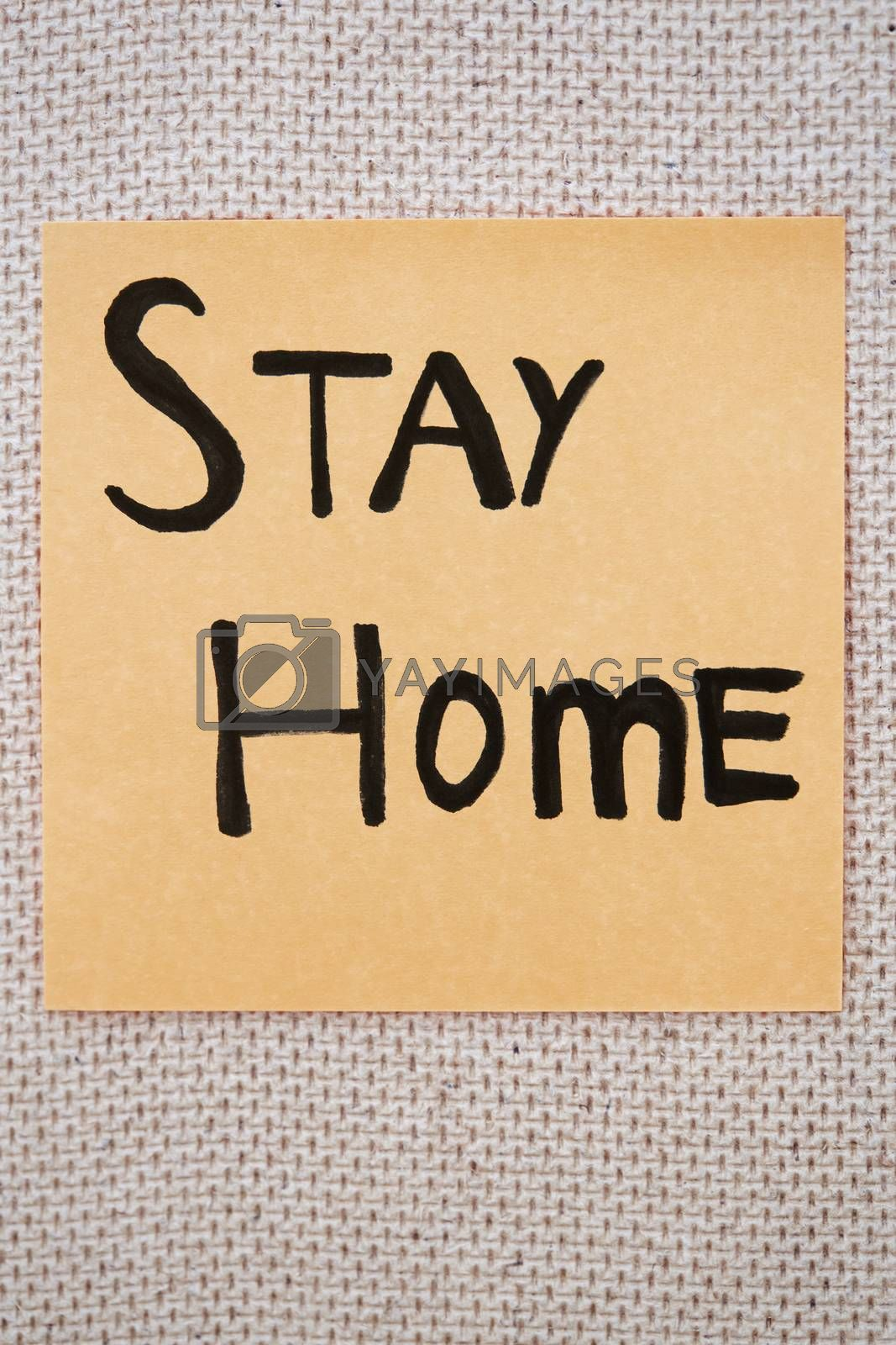 Adhesive note with Stay Home text on a bulletin board