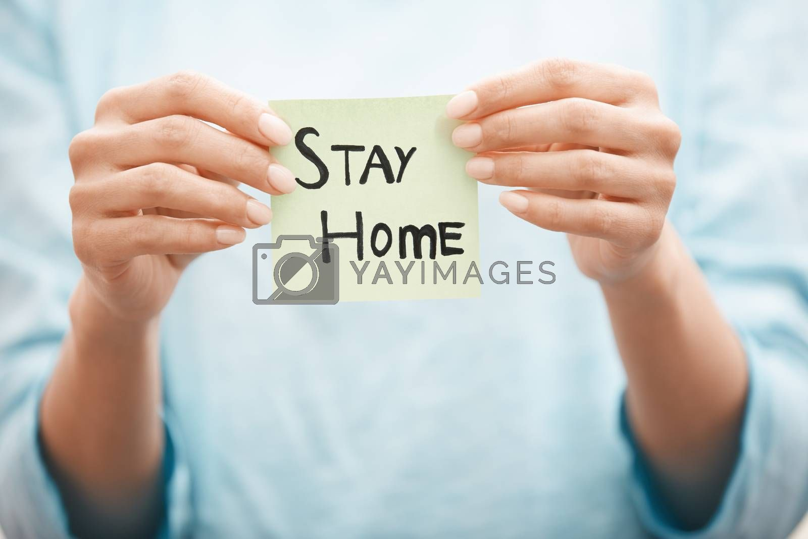 Woman holding adhesive note with Stay Home text